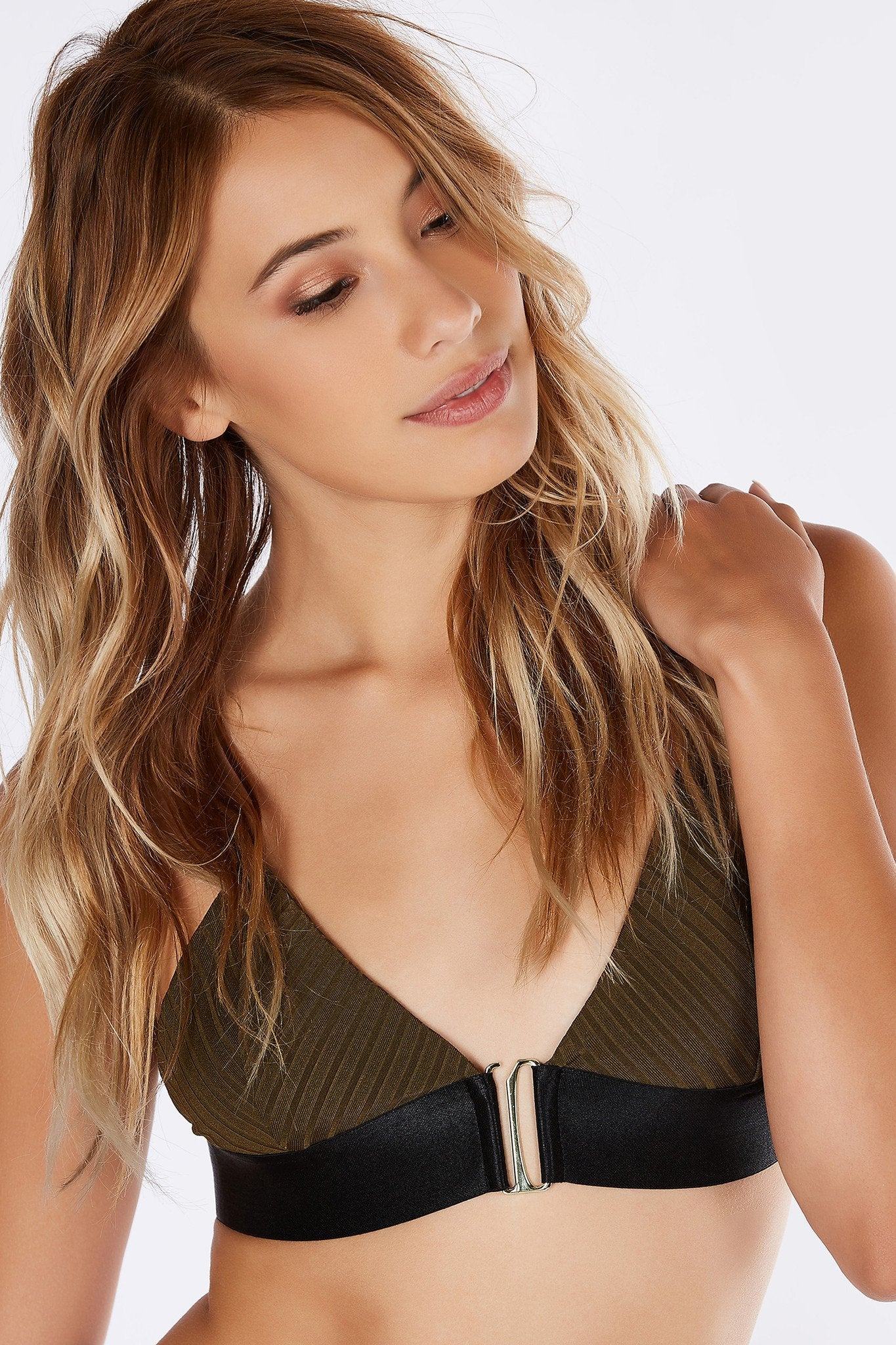 A seductive bralette with a chic front hook closure. Gold hardware detailing for an upscale look. Ribbed material for stretch and comfort. Thick band all around for a smooth finish. Layer with a deep cut top or on its own as a crop top!