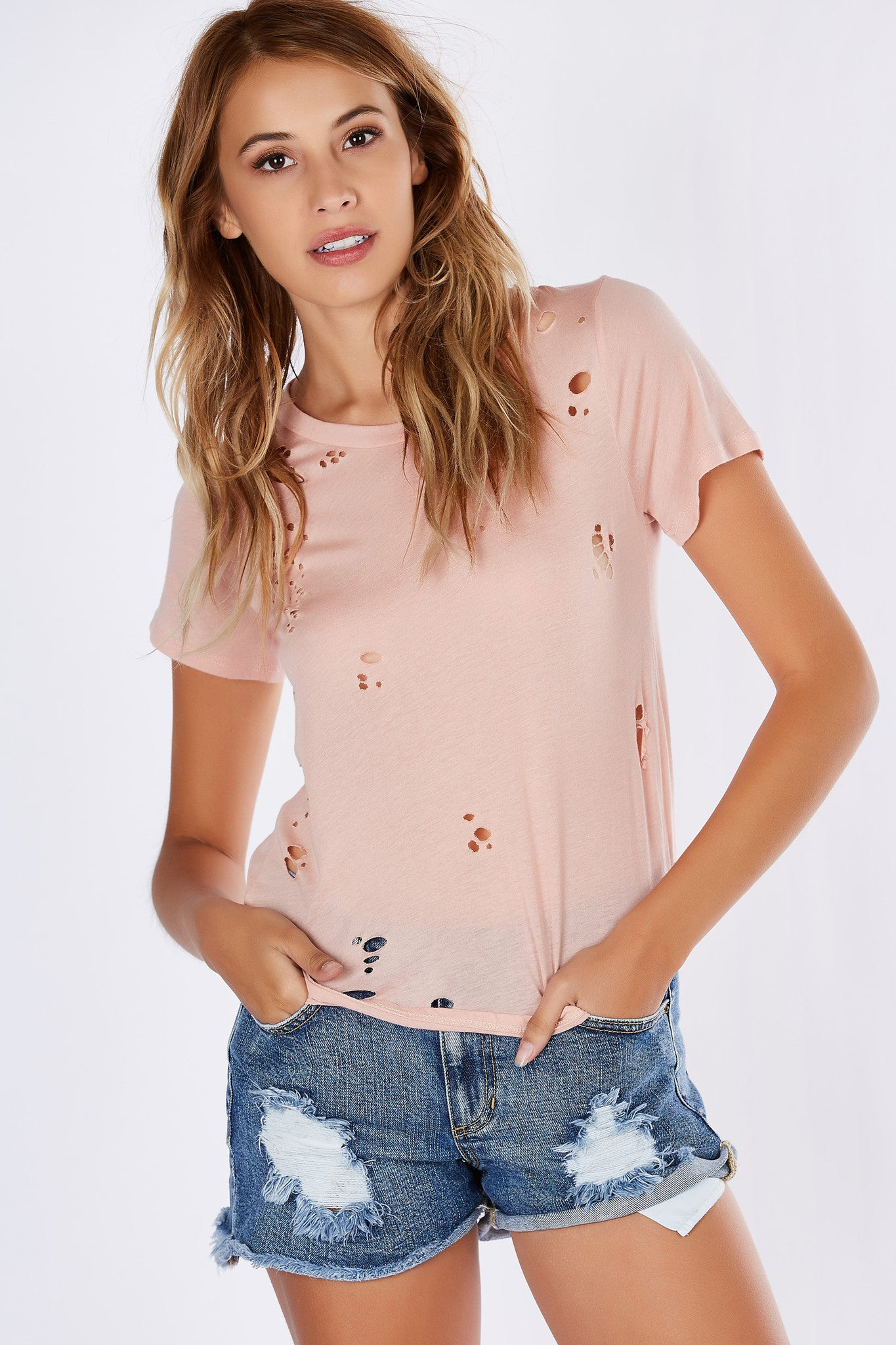 Style those lazy days with this eye-catching distressed knit tee. Sheer and edgy with a scooped out backside. Pair this with a strappy bralette and joggers.