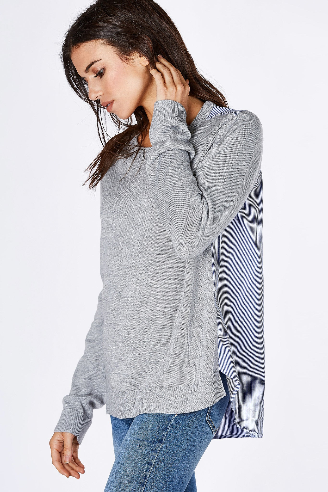 This is not your average top. This stylish piece features a sweater front with long cozy sleeves with a chic contrast back. Faux buttons down the back for a classic blouse design. Easy to style with denim jeans for a smart put together look!