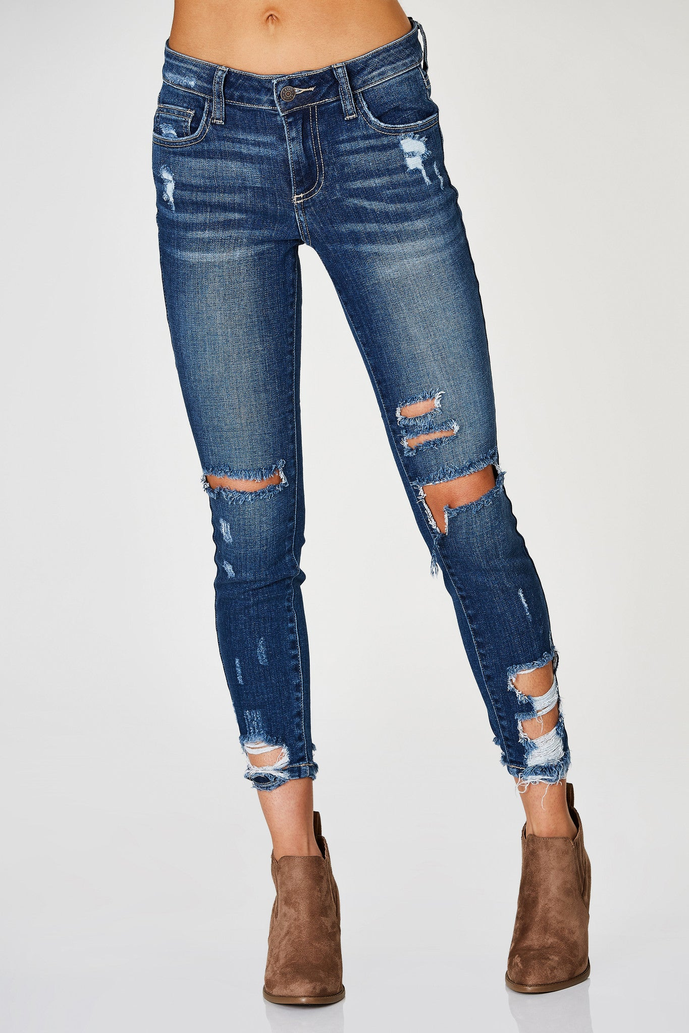 A dope pair of skinny jeans with trendy distressing throughout. Shredded tapered hem with a flattering slim fit. The perfect pair of denims to style with a clean white tee for a girl next door look.