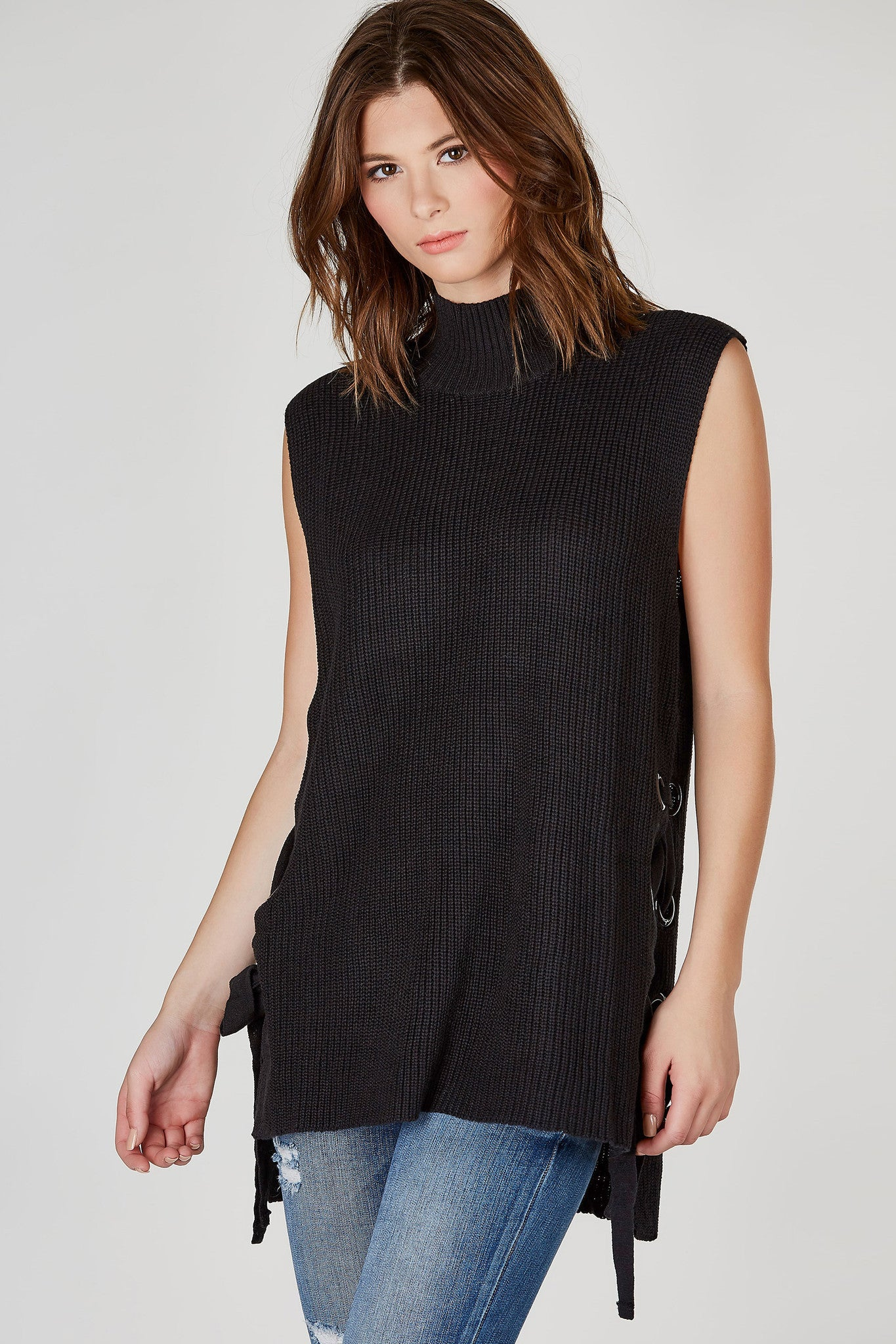 A staple piece every girl should have in their wardrobe. This awesome knit top is great to layer under light jackets for a chic transition into Fall. High, ribbed mock neck with casual sleeveless design. Sides feature trendy lace up detailing for added personality. Pair with your favorite skinny jeans and ankle boots!