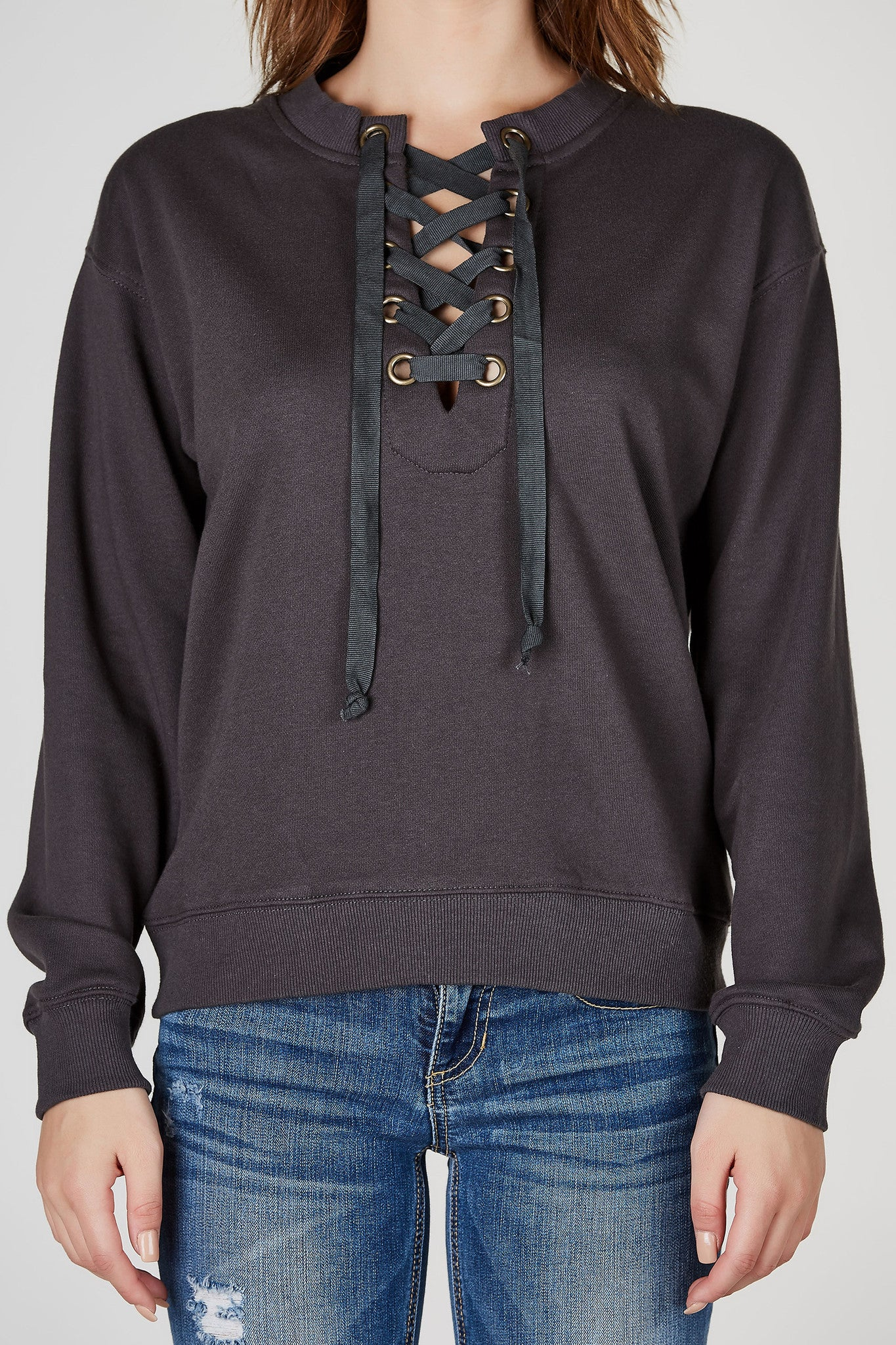 A trendy sweatshirt made for those lazy days when you're in an outfit funk! Awesome lace up neckline with classic ribbed hem all around. Relaxed fit, perfect for a cool laid back outfit. Throw on your favortie skinny jeans and sneakers to complete the look!