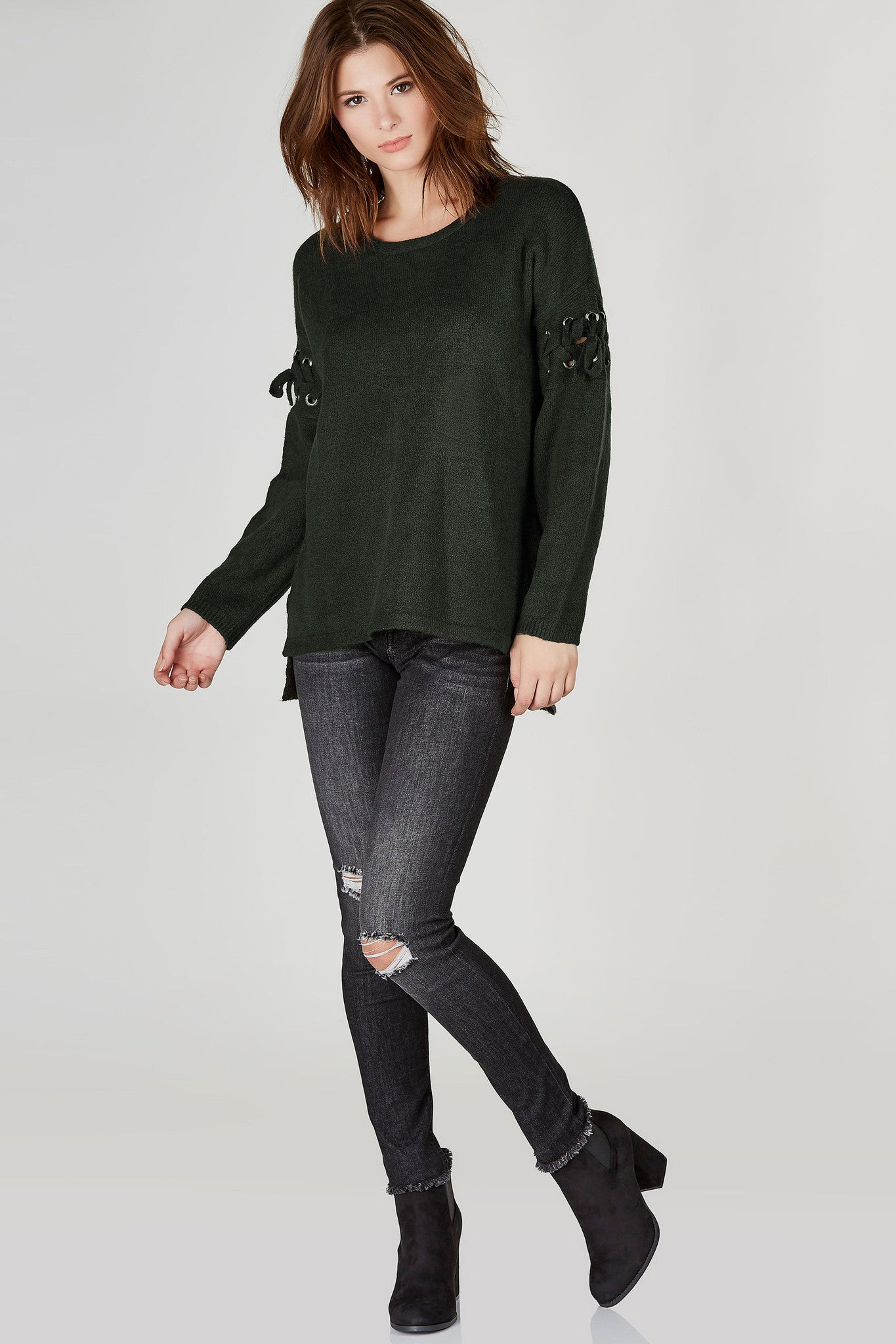 A stylish oversized sweater made of soft stretchy material. Classic crew neck with slightly dropped shoulders for a trendy touch. Features dope lace up detailing on each sleeves with a clean straight hi-low hem.