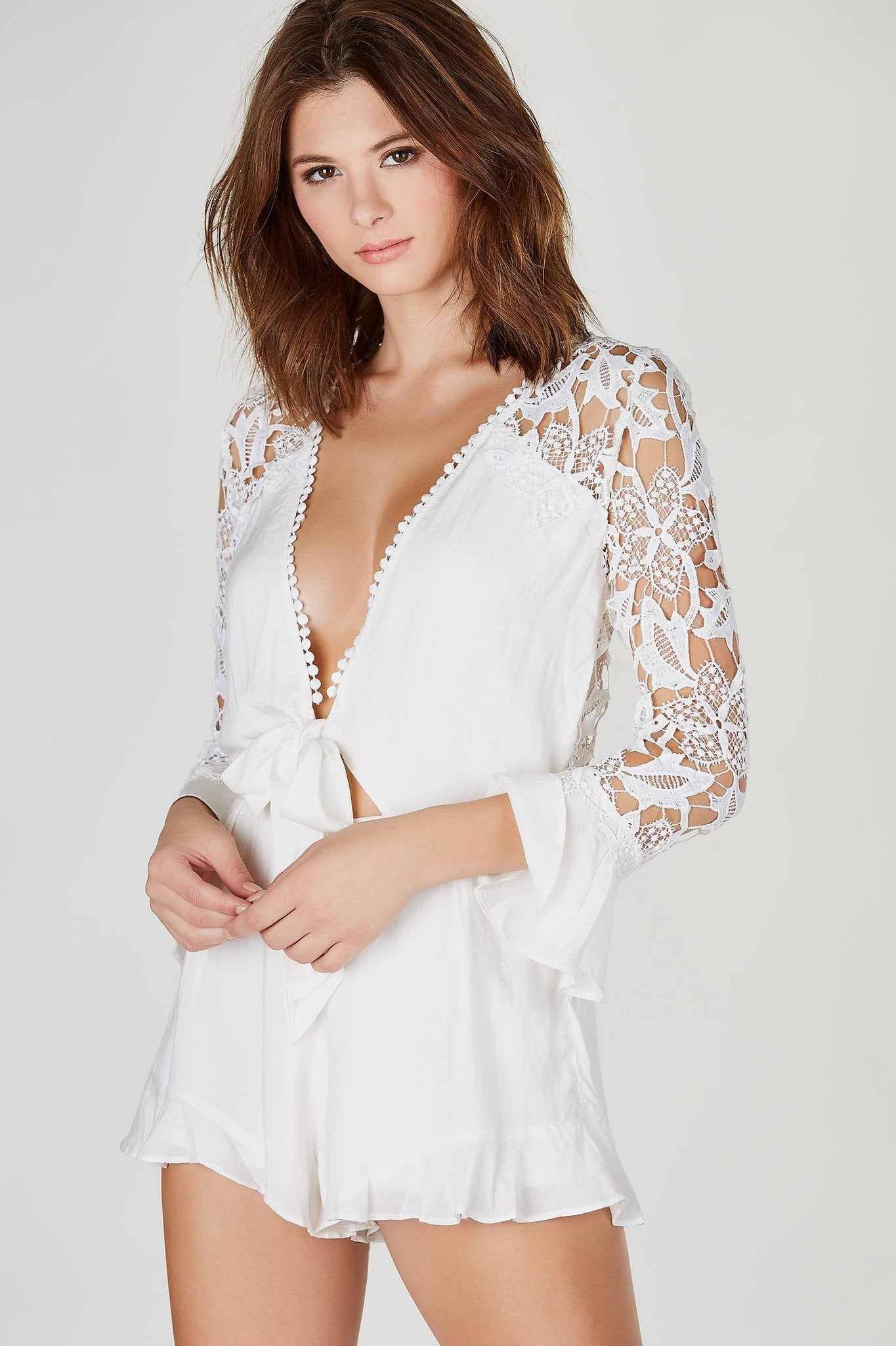This beautiful romper will definitely have all eyes on you no matter where you are! Gorgeous crochet detailing for a revamped, peek-a-boo effect. Open front with a chic tie for closure. Ruffled hem and lining at bottom for an extra feminine touch. Layer a bralette underneath and pair with your favorite pumps!