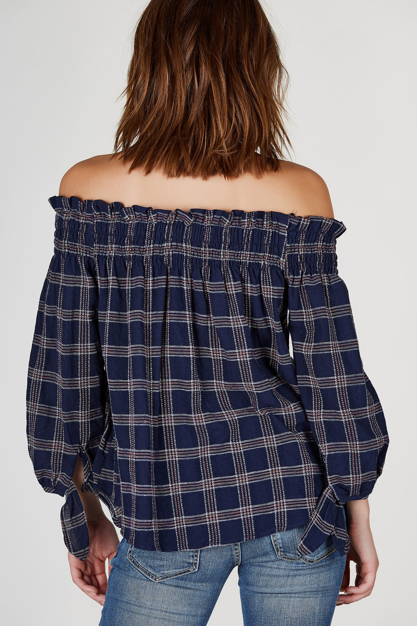 An easy way to look casual but stylish all at the same time! This flirty off shoulder top features plaid patterns throughout with adorable tie up sleeves. Relaxed fit with soft rounded hem with a slightly longer back. Pair with white shorts and sandals!