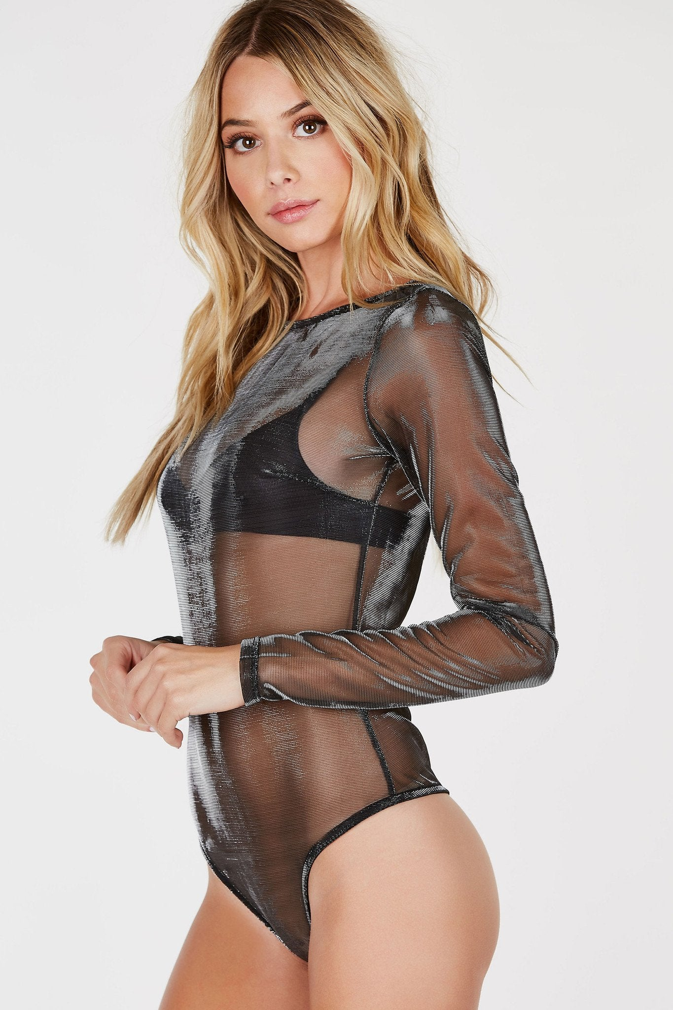 Get your groove on in this ultra chic long sleeve bodysuit! Smooth mesh material throughout with a comfortable cheeky cut with hook and eye closure. Rounded neckline with a slim fit all around. Layer a strappy bralette underneath with some faux leather pants and pumps for a sassy nighttime look!