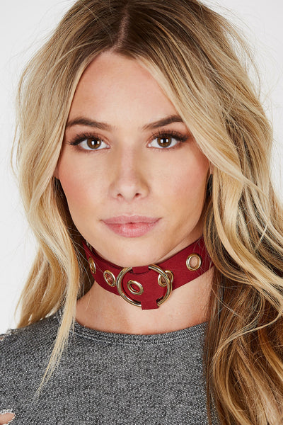 A trendy wide band choker with awesome eyelet detailing all around. Bold buckle at center for adjustable fit and style. Wear it in the front to show off the extra hardware or in the back for a cleaner finish.