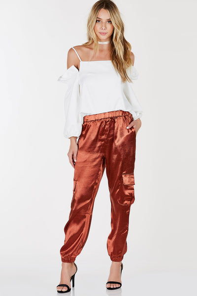 Joggers couldn't get sleeker than this! These trendy pair of pants feature cargo style pockets with a classic elasticized waistband and hem. Gorgeous satin finish to dress up your look effortlessly. Style with a bodysuit and a pair of heels!