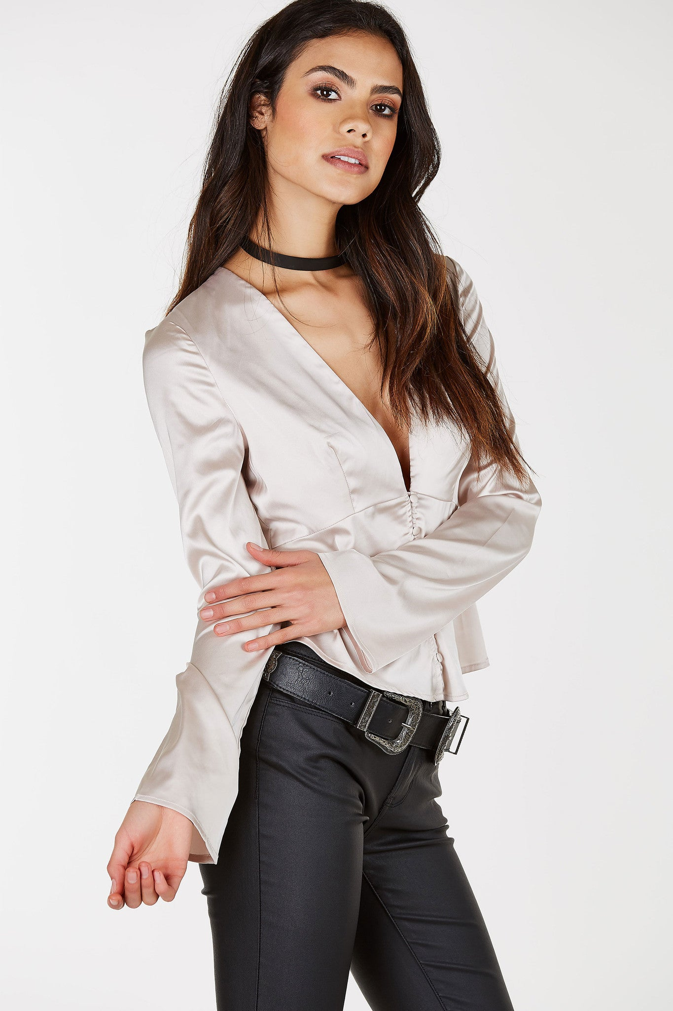 A smooth satin finish blouse with relaxed long sleeves to welcome the new Season. Dainty button detailing down the front with a bold deep cut neckline. Layer a lace bralette underneath and style with classic blue denims and heeled booties!