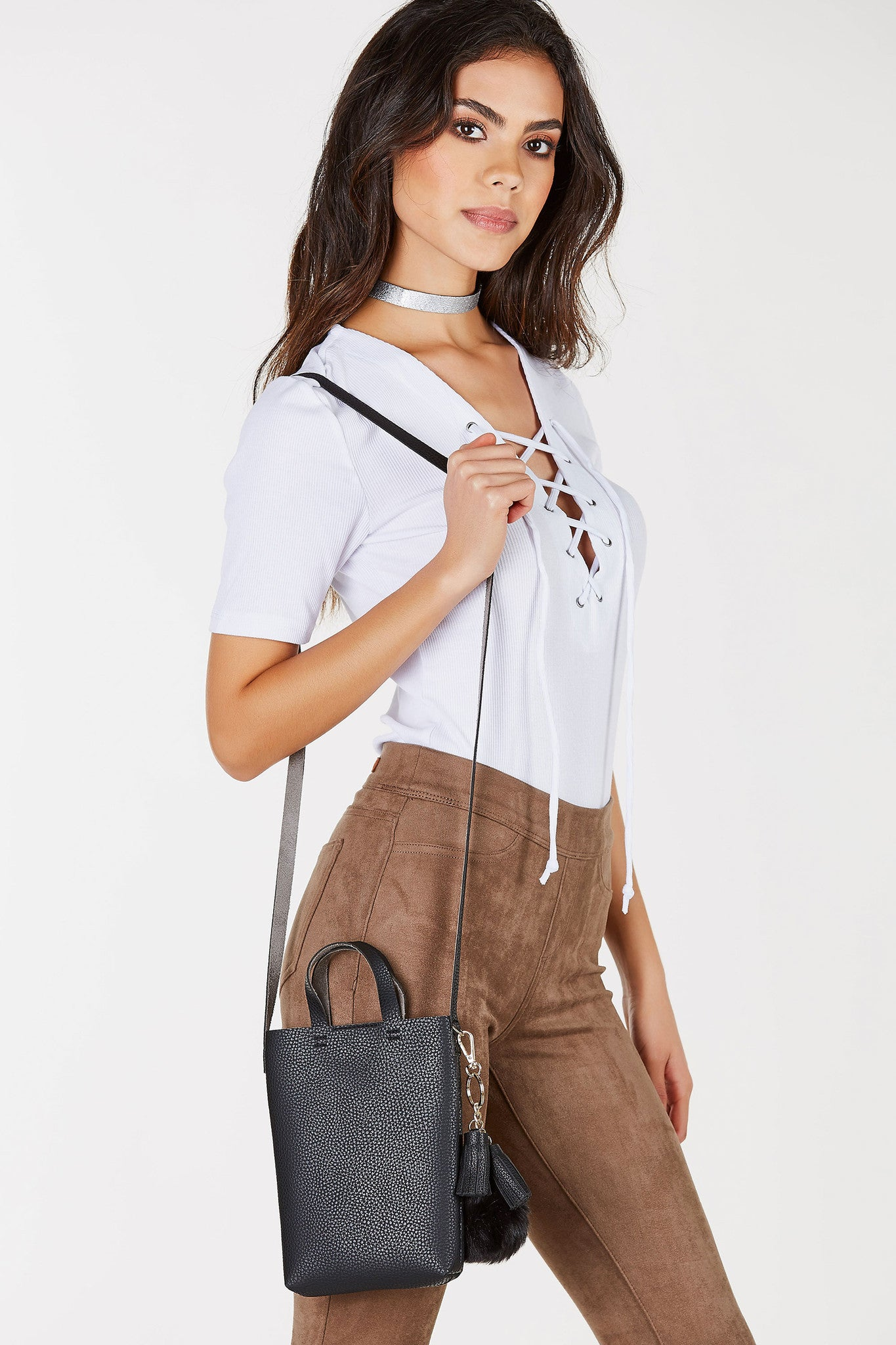 An adorable mini crossbody purse with faux fur pom pom and tassels attached for a flirty detail. Chic faux leather exterior for a classy vibe. Dainty handles at top with clean shoulder strap and magnetic closure. The perfect addition to your basic day to day outfits for functionality and style!