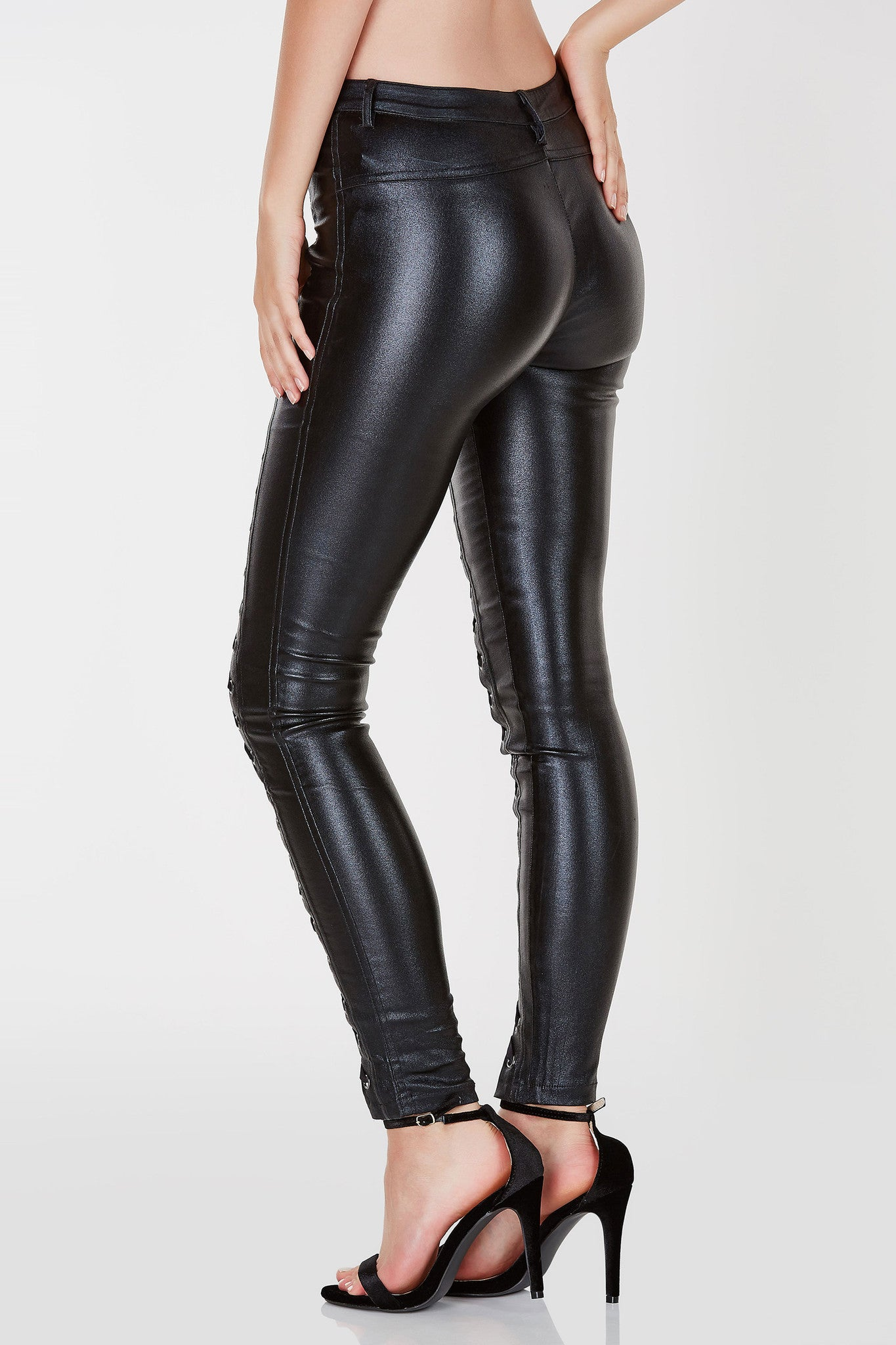 Faux leather finish skinny pants. Lace up detailing down the front on each leg. Single zip and button closure.