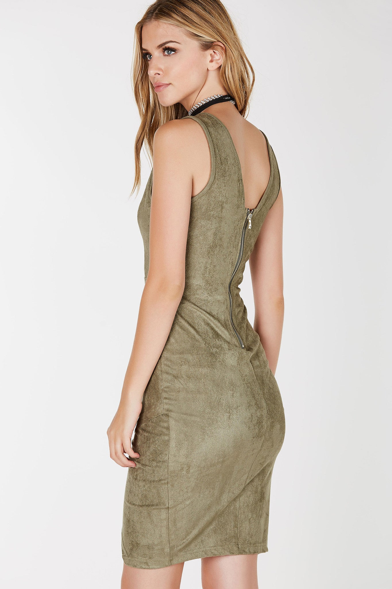 Sleeveless with deep V-neckline. Cut out at center with envelope hem. Suede finish and exposed zipper closure.
