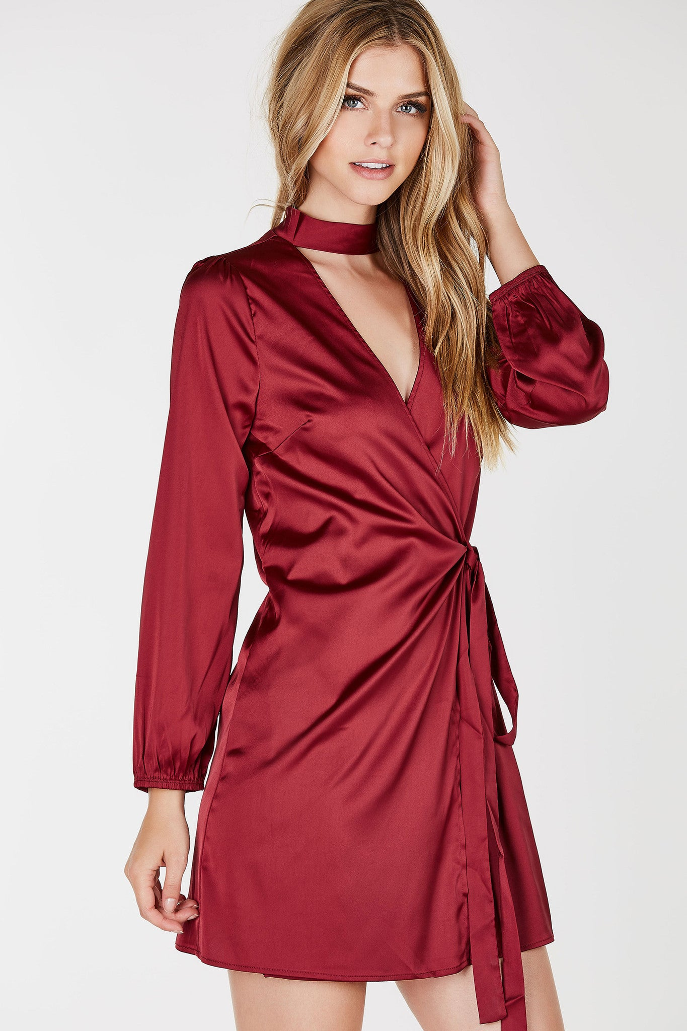 Long sleeve satin finish dress with wrap design. Front tie closure with choker neckline and deep V-cut out.