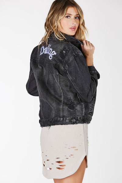 Dark wash denim jacket with distressing throughout. Graphic in back with raw hem all around.