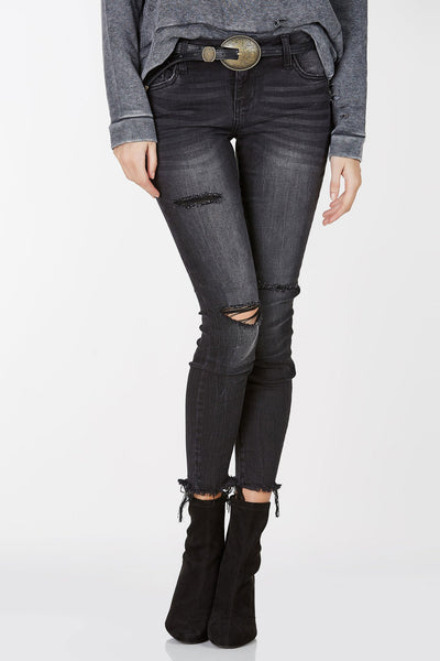 Faded dark wash skinny jeans with distressing in front. Frayed raw hem with button and zipper closure.