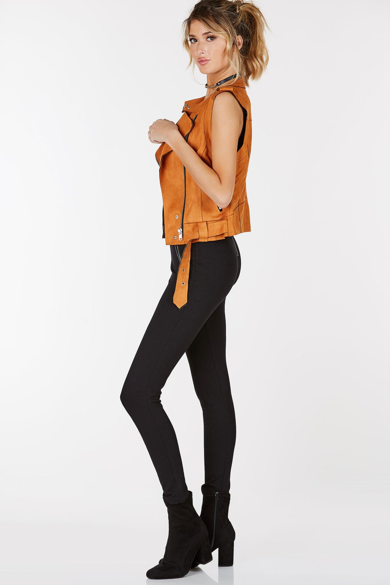 Suede moto vest with asymmetrical front zip closure. Side pockets with silver hardware detailing.