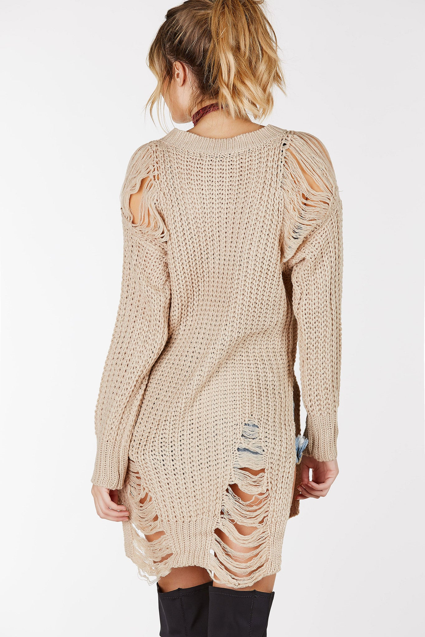Crew neckline loose knit sweater. Oversized fit with shredded detailing and side slits.