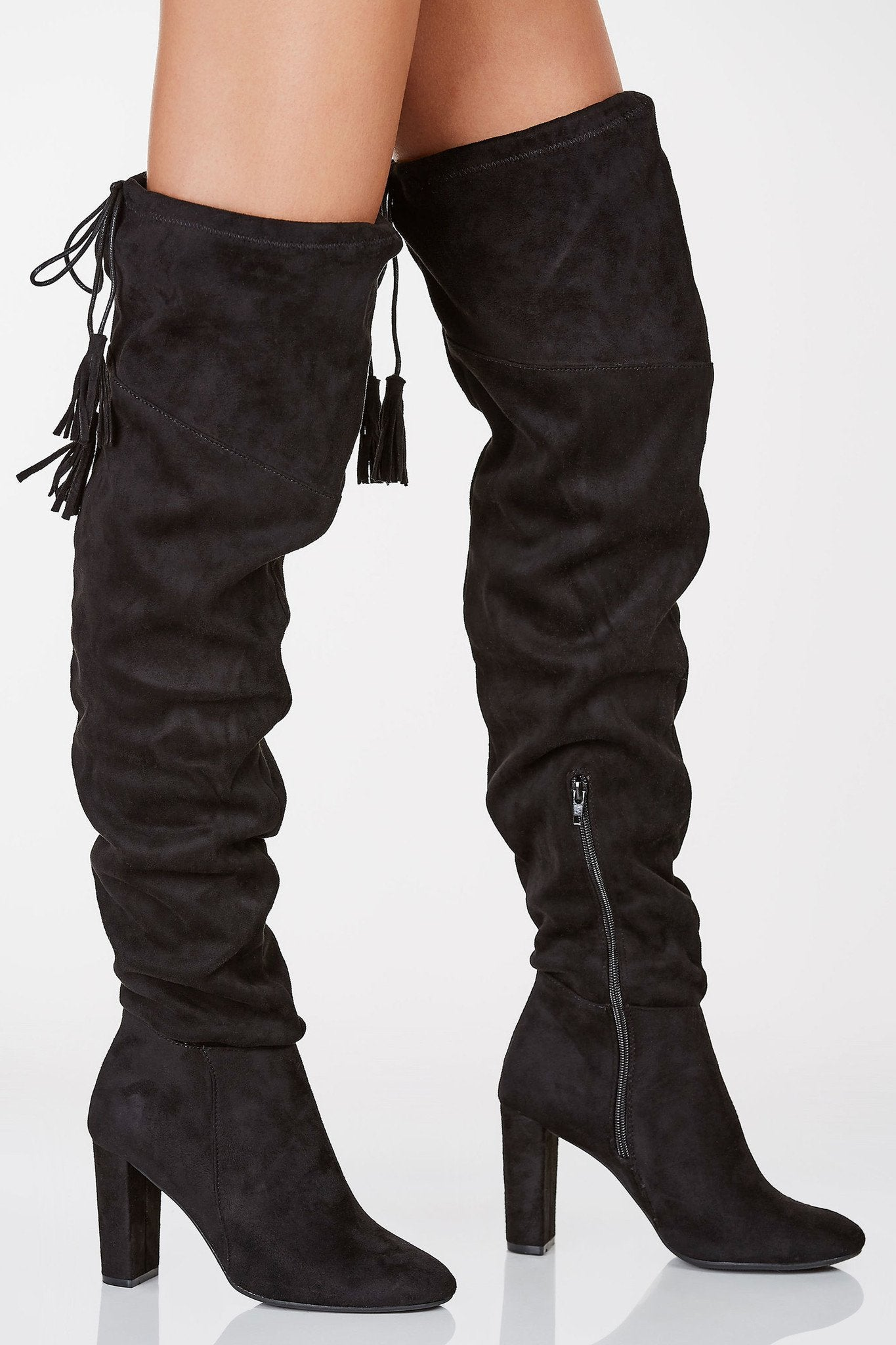 Suede finish thigh high boots with soft rounded toe. Block heels with side zip closure and tassel detailing.