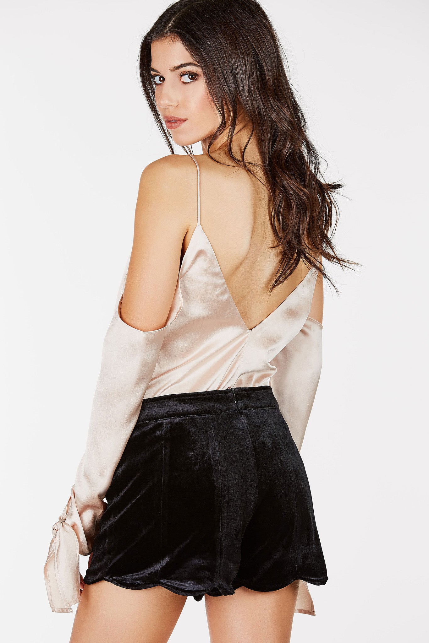 Silky, long sleeved top with cold shoulder and wrist ties.  Pair with jeans for a casual date night outfit.