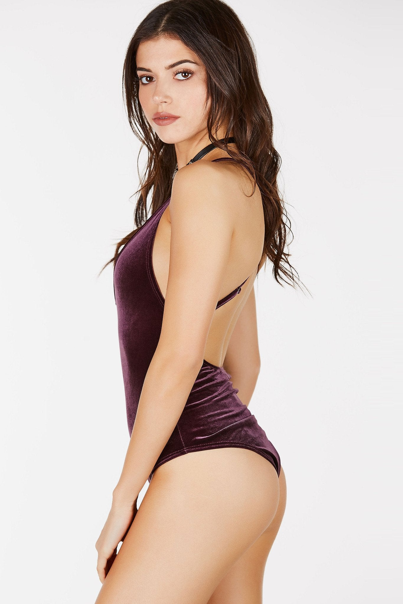 Sleeveless bodysuit with adjustable shoulder straps that criss crosses at the back. Velvet finish with V-neckline. Cheeky cut with snap button closure.