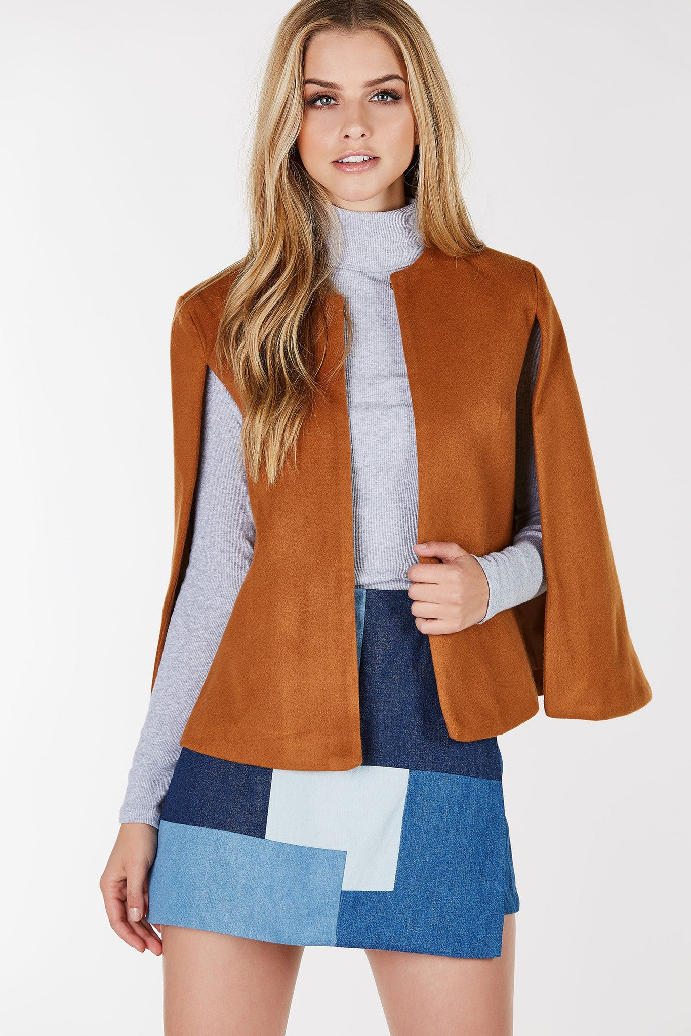 Round neck cape jacket with slits for each arm. Open front with straight hem alla round.