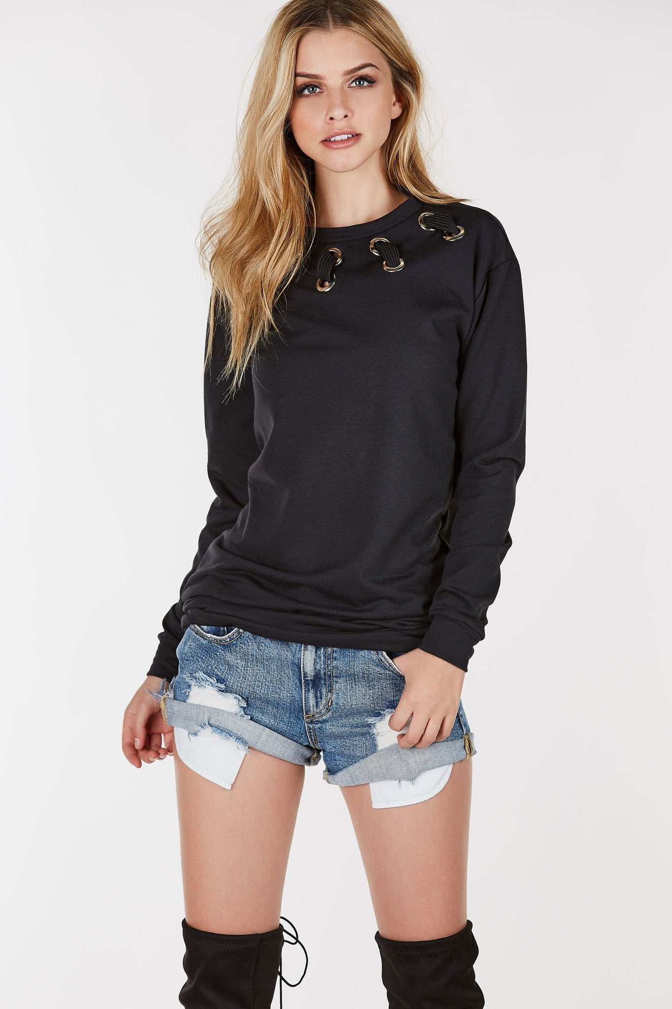 Round neck long sleeve sweater tunic with eyelet detailing and lace up design. Relaxed fit with straight hem all around.