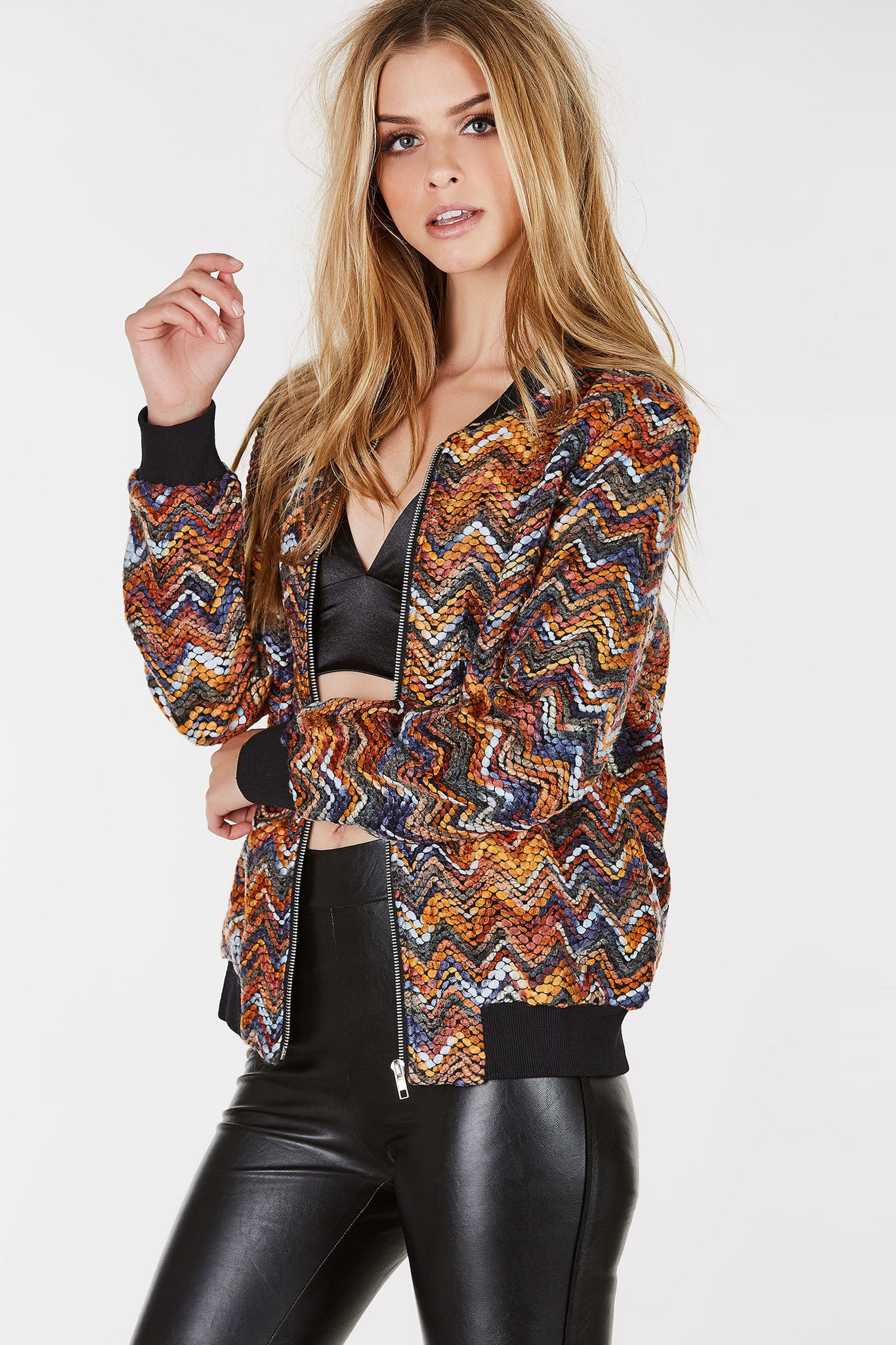 Long sleeve bomber jacket with multi colored chevron patterns throughout. Front zip closure with ribbed hem.