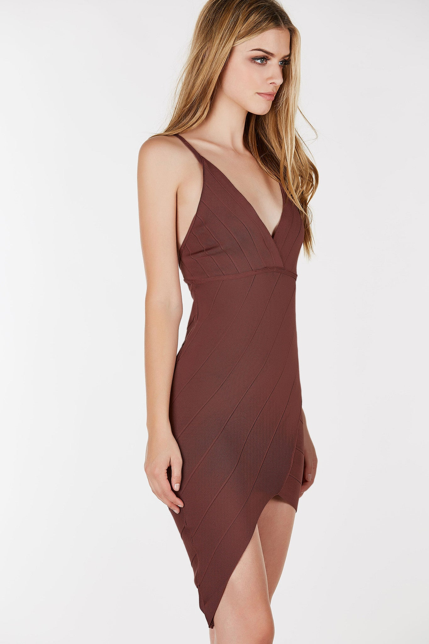V-neckline bandage dress with asymmetrical hem. Dainty shoulder straps that criss crosses at back with zip closure.