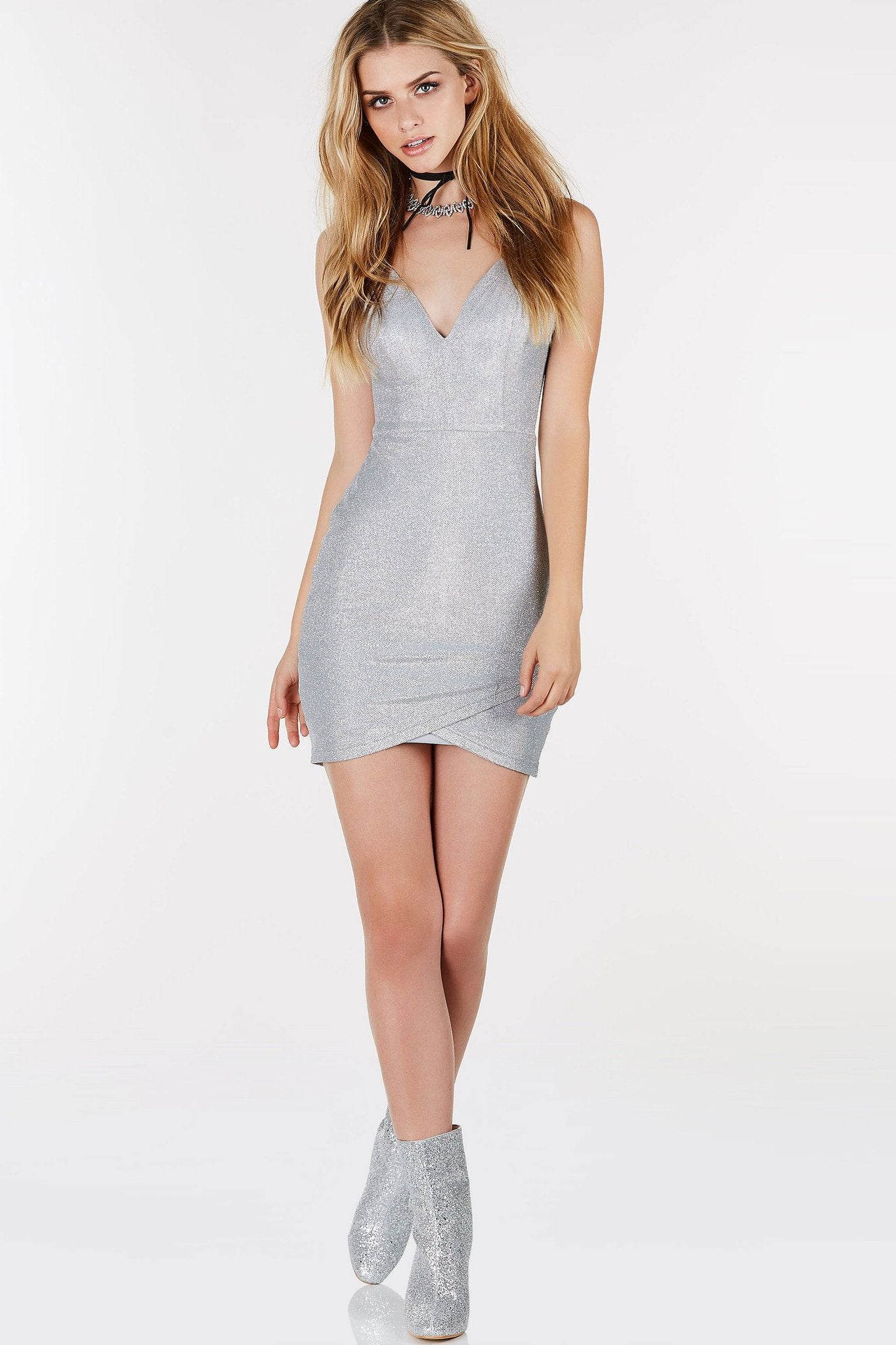 Deep V-neckline mini dress with open back and strappy detailing. Envelope style hem with glitter finish throughout.