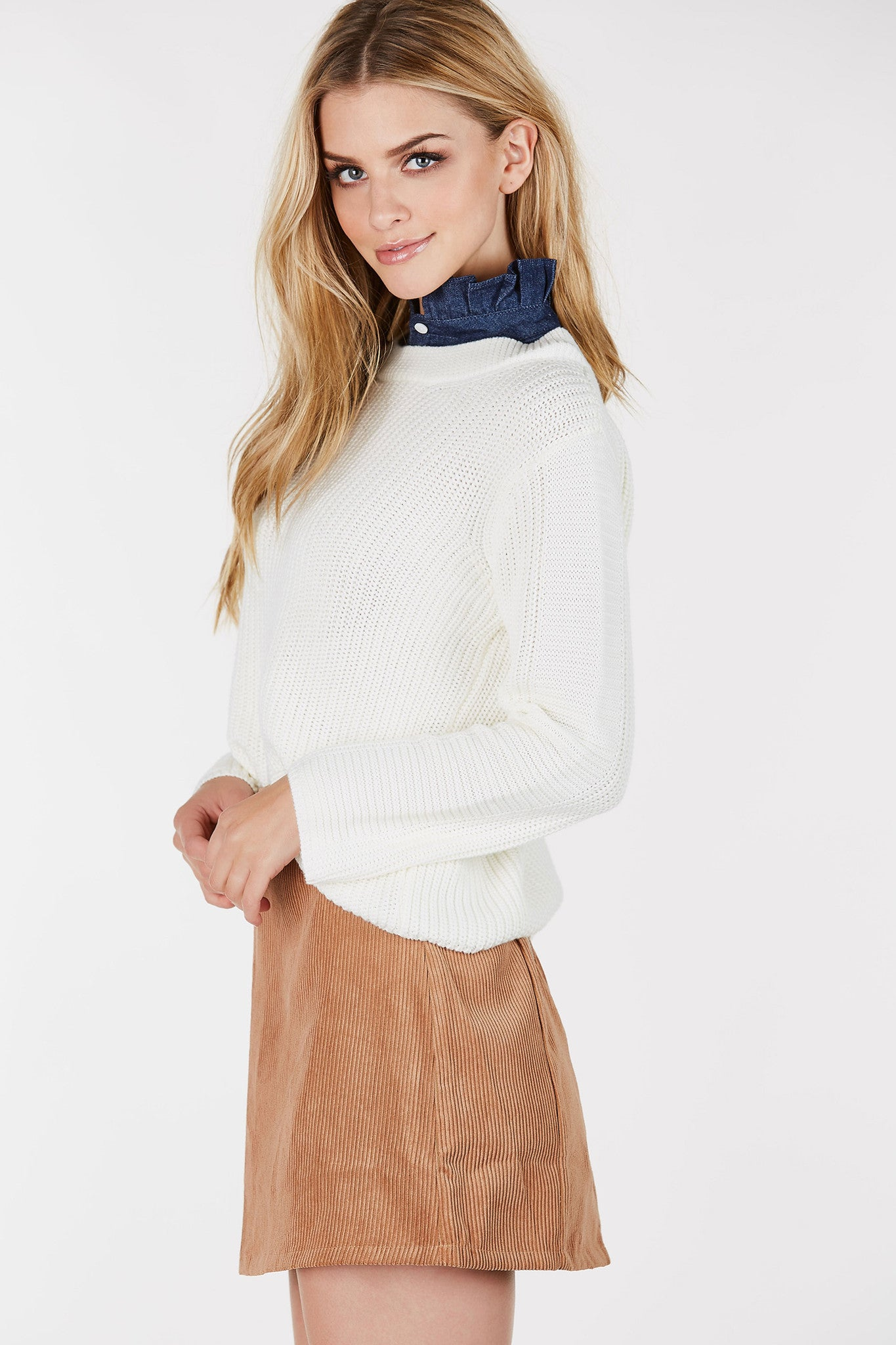 Mock neck top with sweater knit body. Contrast neckline with ruffle detailing.