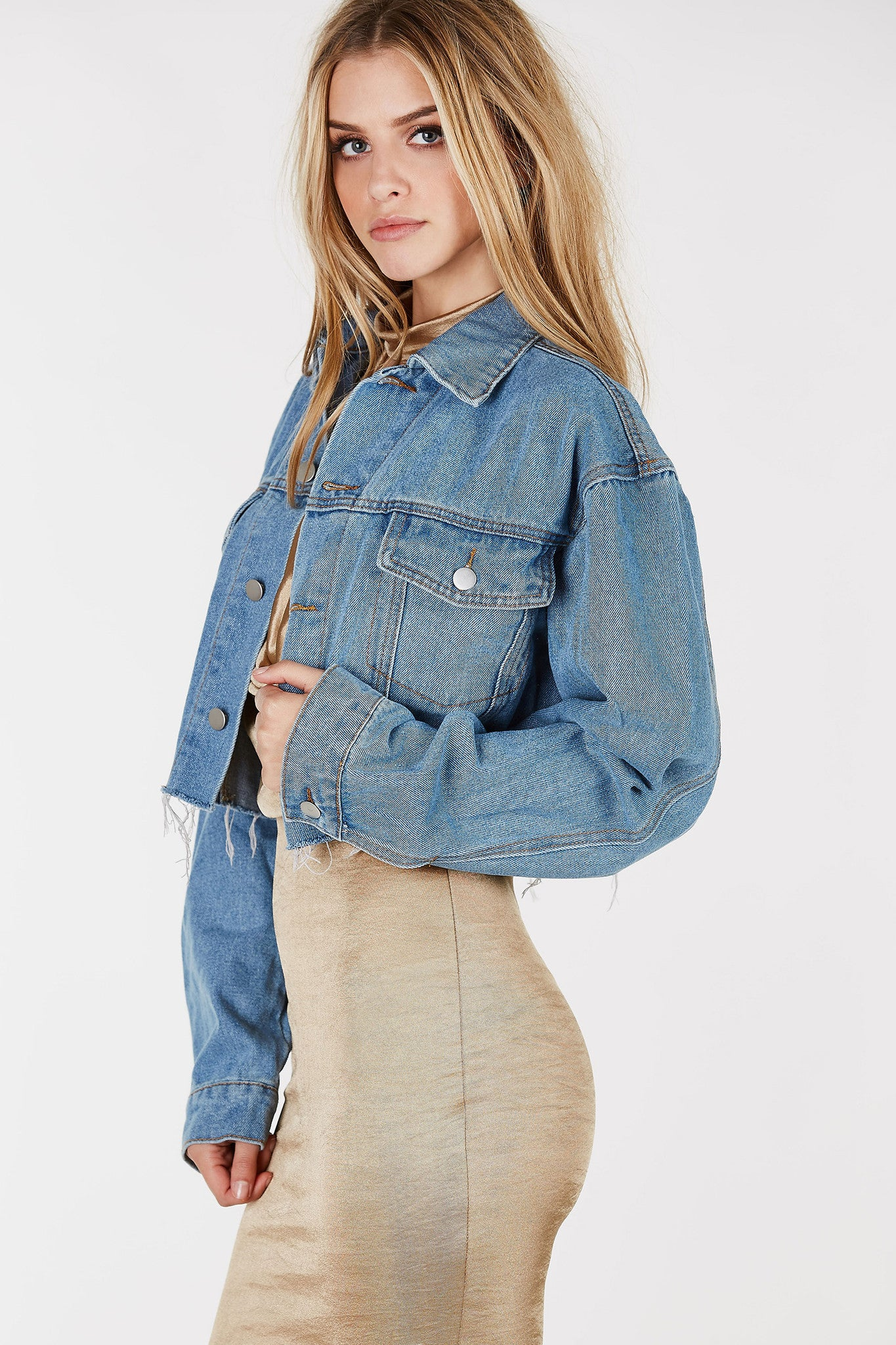 Classic denim jacket in medium wash. Cropped raw hem all around with button closure.