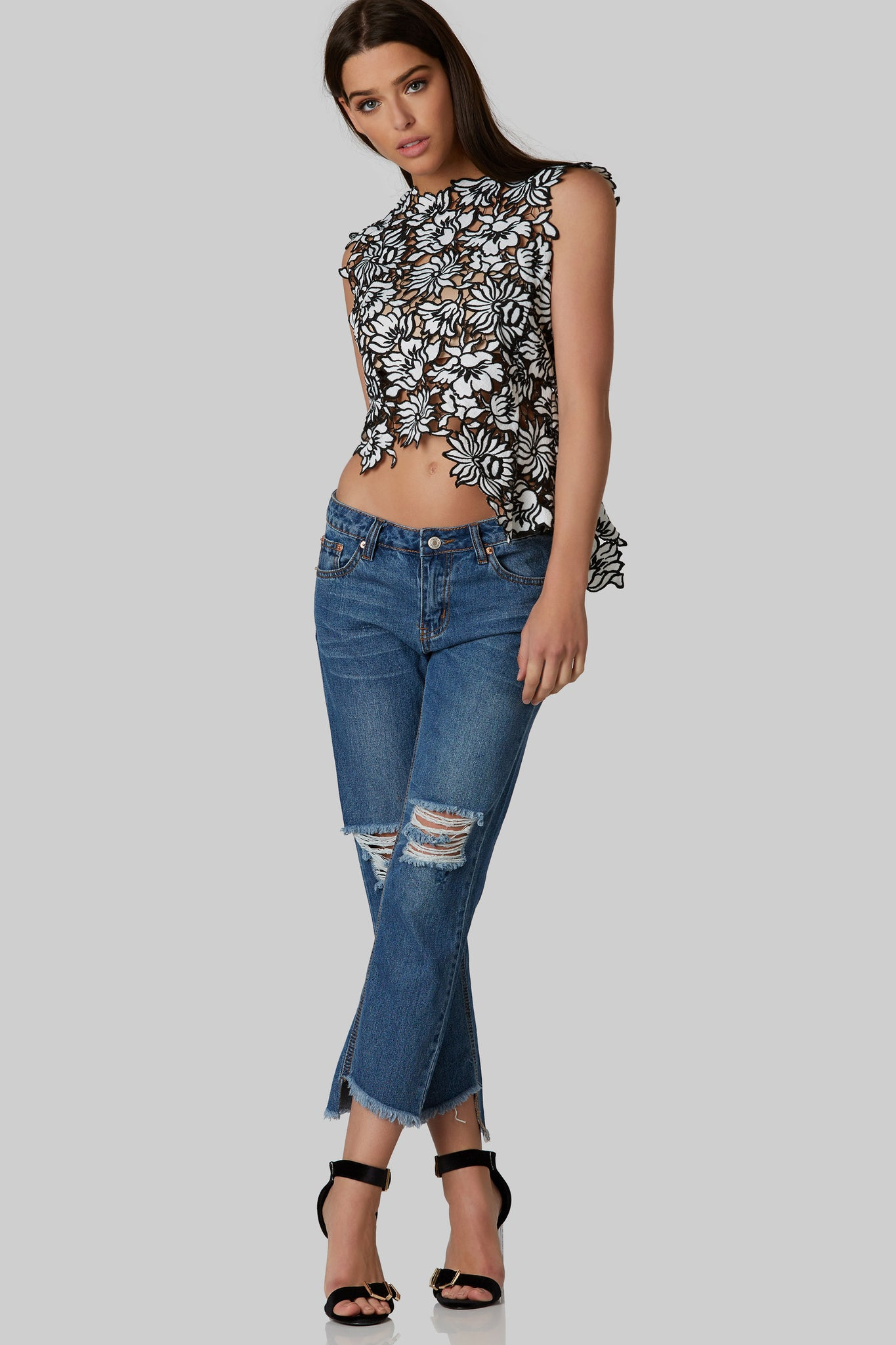 Bold sleeveless top with crochet floral detail throughout. Hidden back zip closure with cropped nude lining attached,