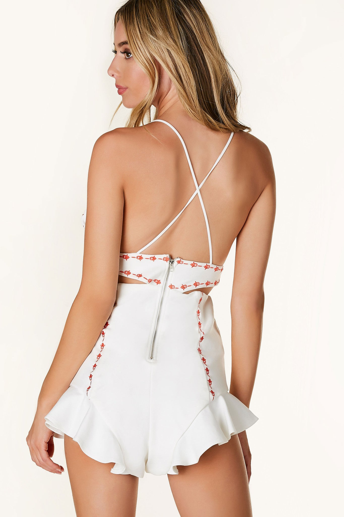 Flirty sleeveless romper with V-neckline and bold cut outs. Embroidered detailing and ruffle time with exposed back zip closure.