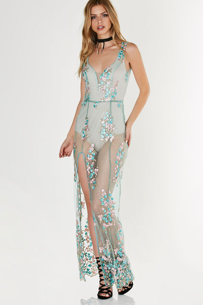 Elegant mesh maxi dress with intricate floral patterns throughout. Nude bodysuit lining with front slit for added detail and cut out in back.