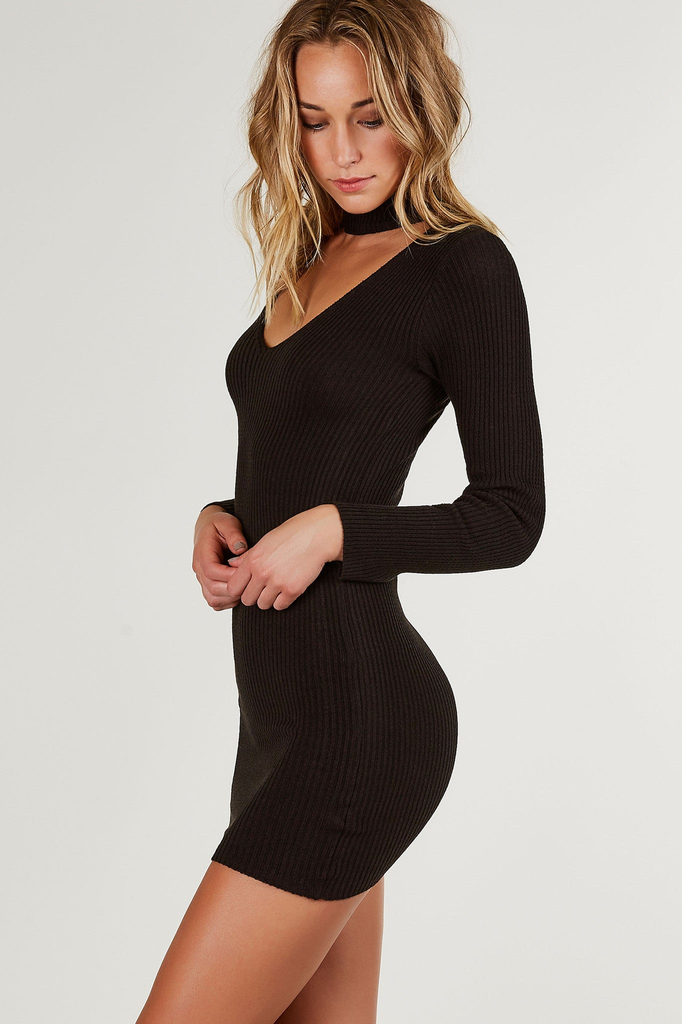 Long sleve ribbed mini dress with trendy choker neckline and V-shape cut out in front. Stretchy material with bodycon fit and straight hem all around.
