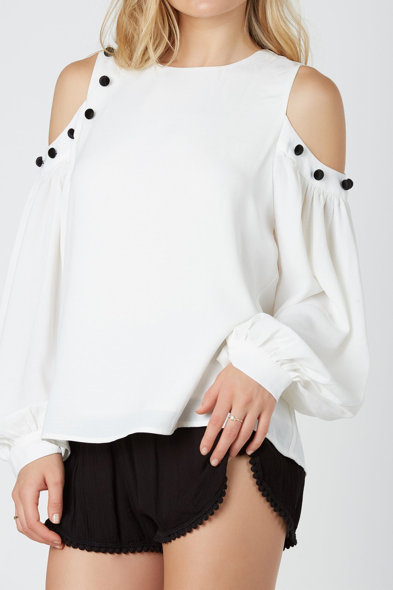Long sleeve cold shoulder top with rounded neckline. Fully lined with relaxed fit and velvet button detailing.