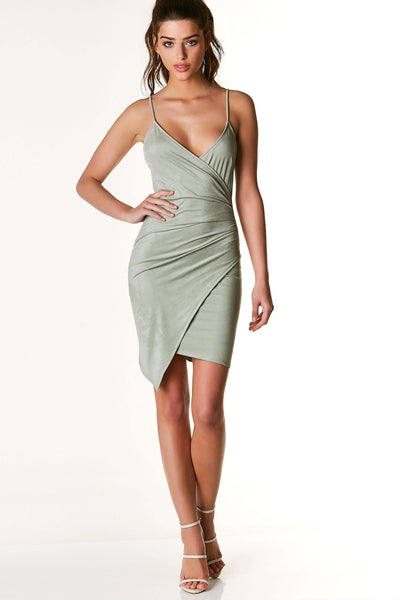 Sexy sleeveless mini dress with chic wrap style V-neckline. Ruched on one side with asymmetrical envelope hem. Soft suede finish all around with stretchy, bodycon fit.