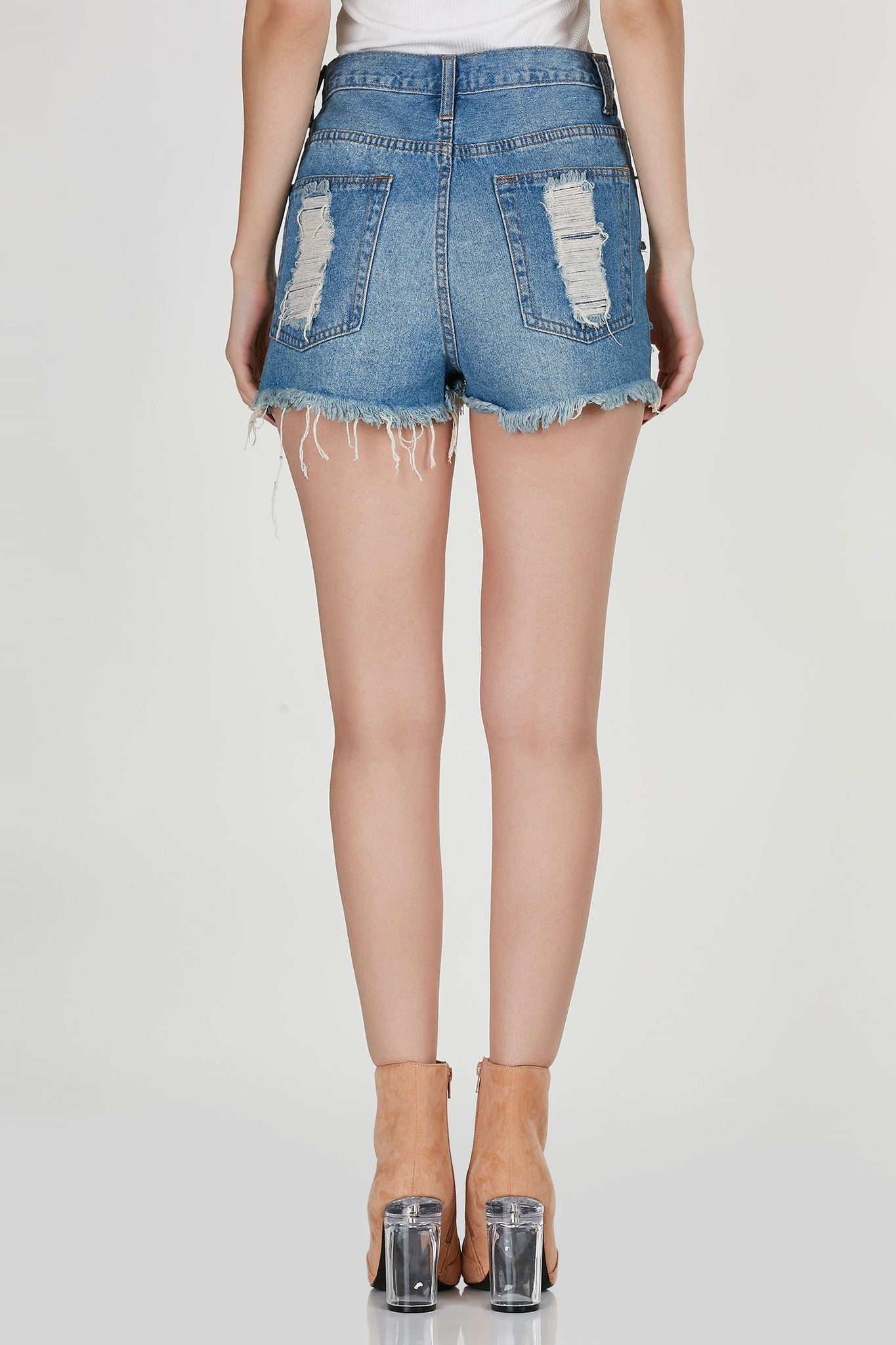 Your new favorite pair of ripped denim jeans. There is no such thing as too many high waisted shorts! These awesome pair features serious distressing in front with shredding in the back. Five functional pockets with single zip and button for closure. Will go well with any crop tops in your closet!