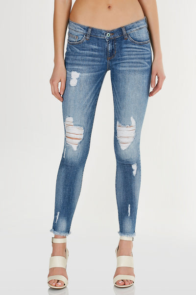 Classic low rise skinny jeans with faded wash and distressing throughout. Frayed raw hem with button and zip closure.