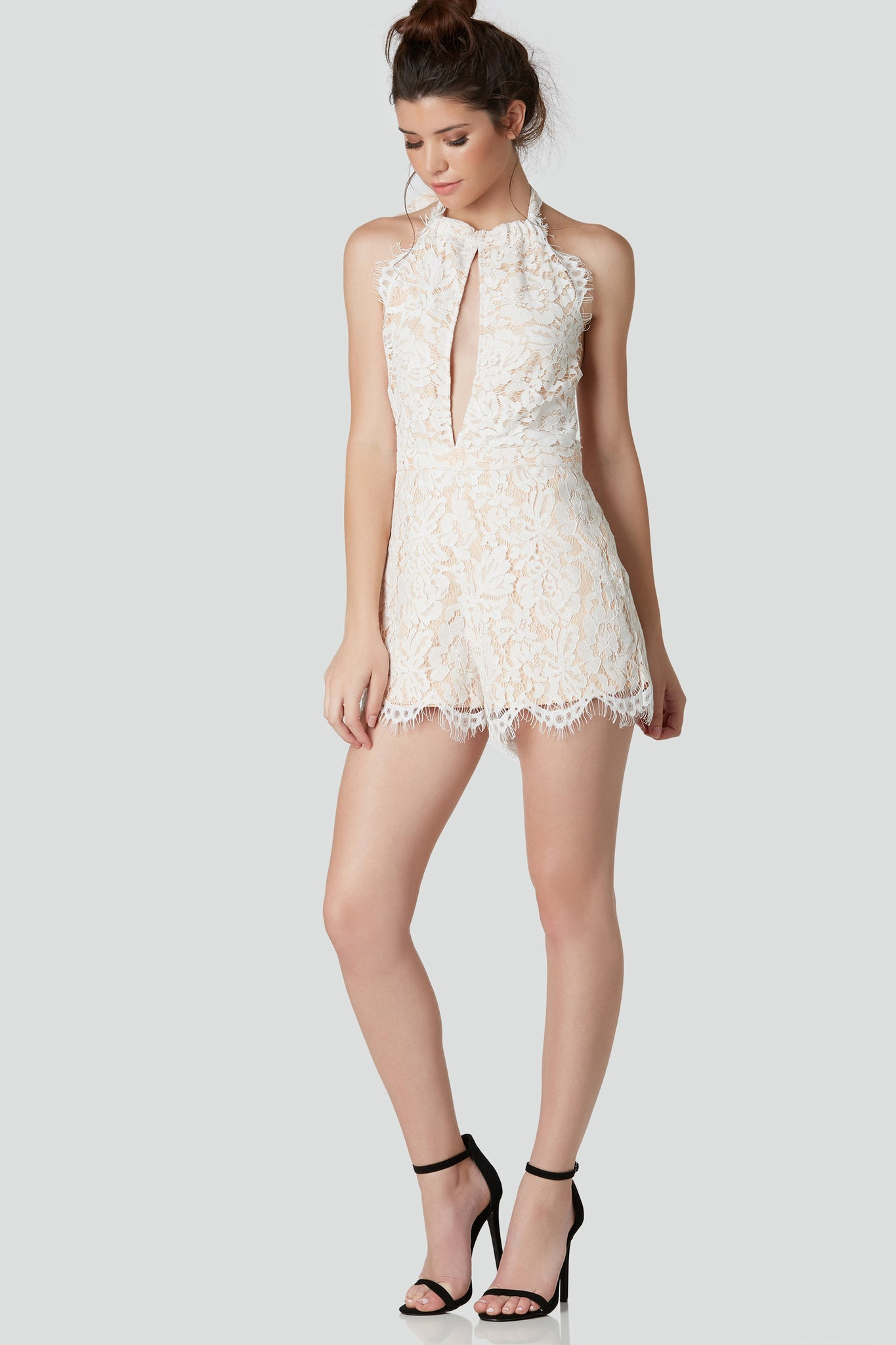 Elegant sleeveless romper with flattering halter neckline and bold keyhole cut out in front. Nude lining with lace overlay with eyelash trim detailing and back zip closure.
