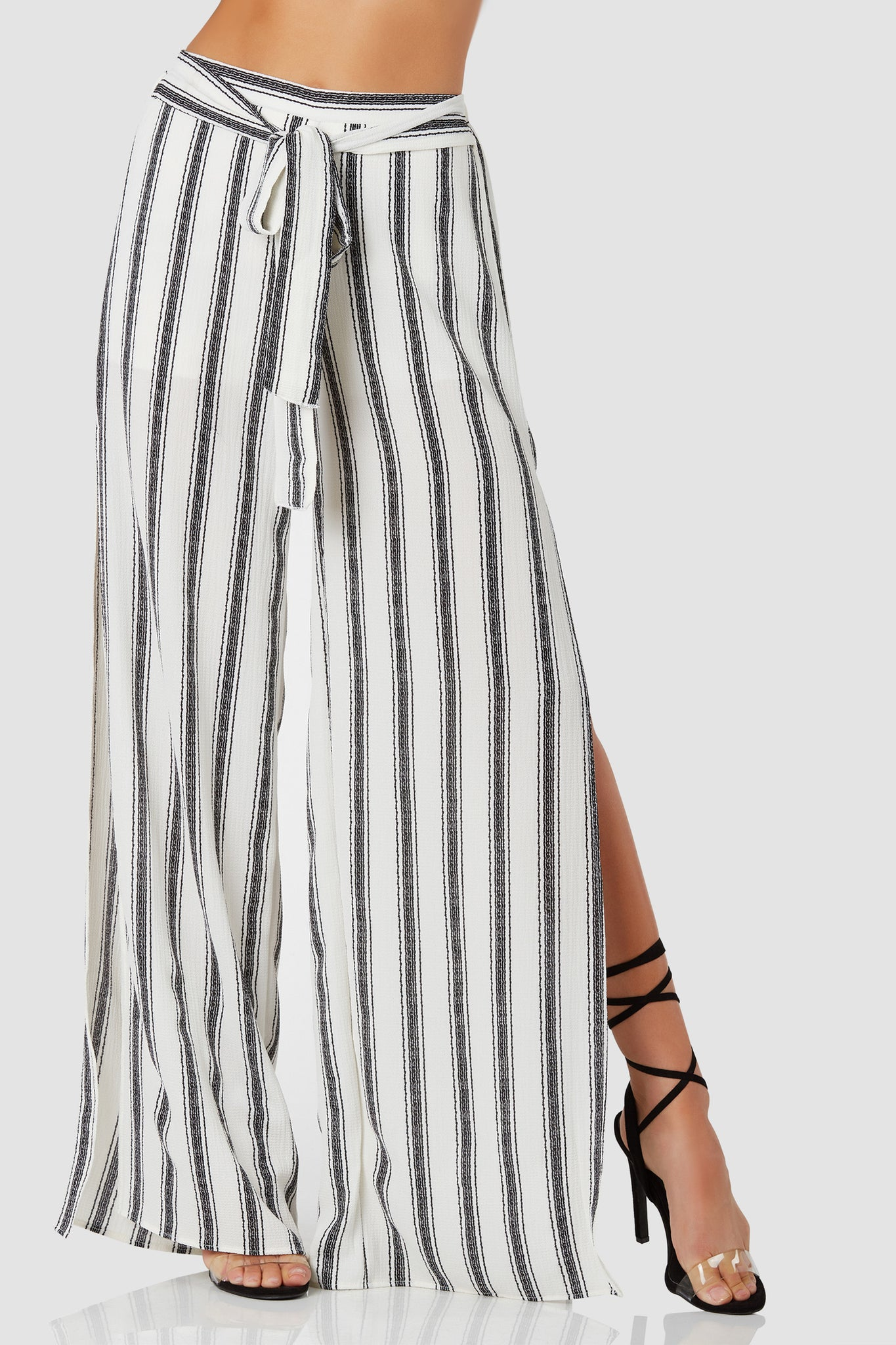 Chic high waist slacks with stripe patterns throughout. Waist tie detailing with bold side slits.