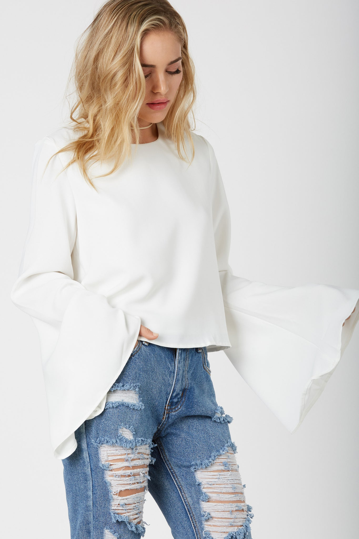 Chic long sleeve top with round neckline and flowy bell sleeves. Oversized fit with cropped hem finish.