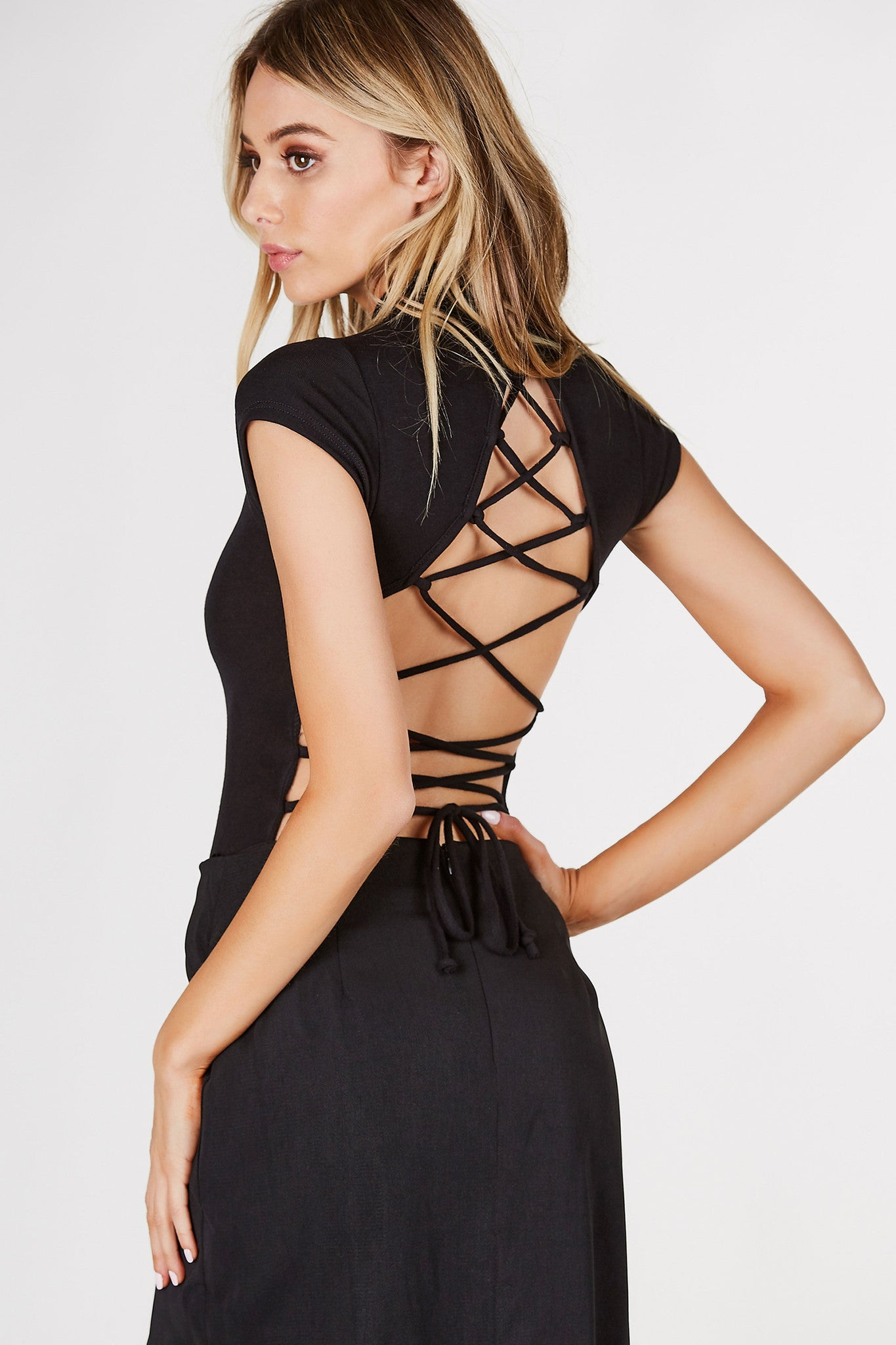 Mock neck bodysuit with cap sleeves. Open back with sexy lace up design. Cheeky cut with snap button closure.