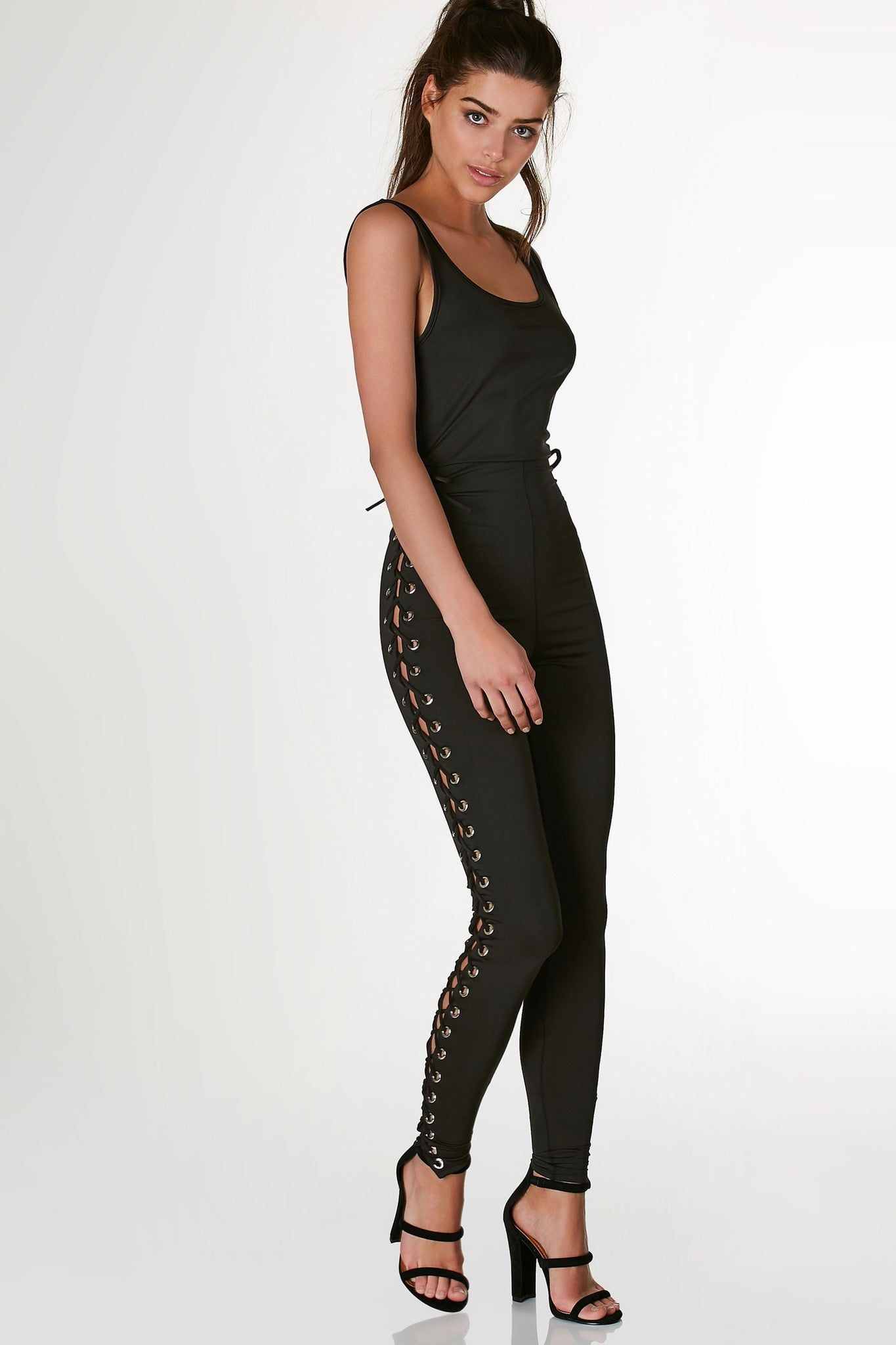 Sexy sleeveless jumpsuit with U-neckline and bodycon fit. Bold cut out down each side with lace up design and eyelet detailing.