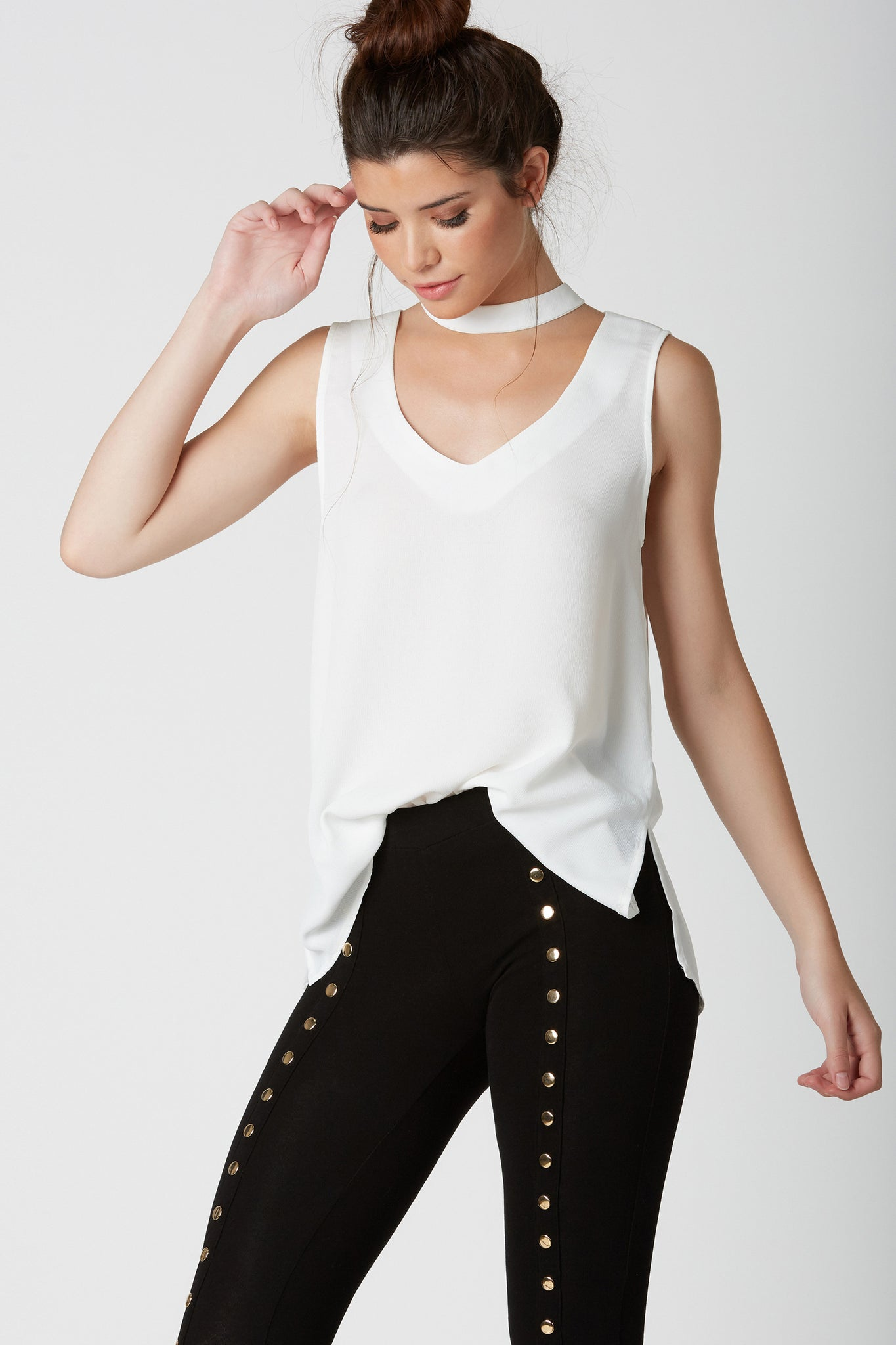 Chic sleeveless blouse with cut out choker neckline. Lightweight material with relaxed fit and button closure in back.