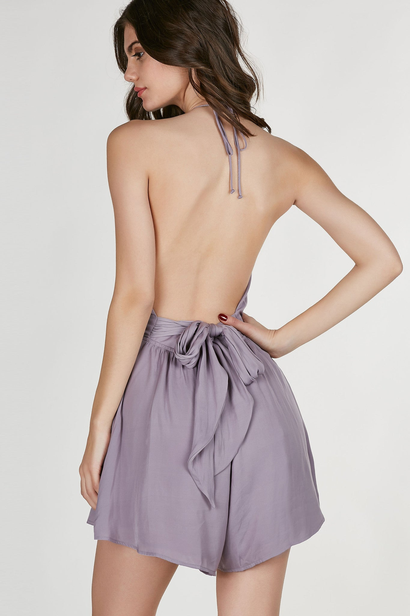Flowy halter romper with cross over finish at bust. Peek-a-boo design at center with open back and tie at wasit.