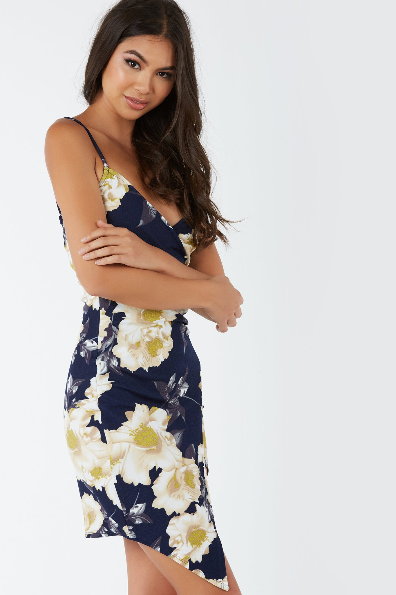 Sleeveless V-neck enveloe dress with wrap design. Floral print throughout with bodycon fit.