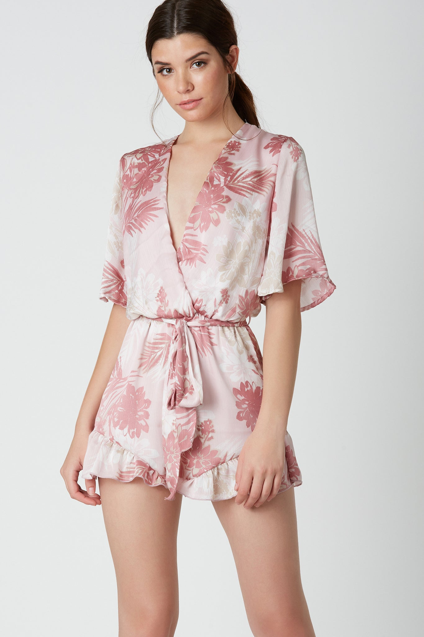 Lightweight short sleeve romper with overlap neckline and waist tie detailing. Floral print throughout with ruffle trim at hem and smooth satin-like finish.
