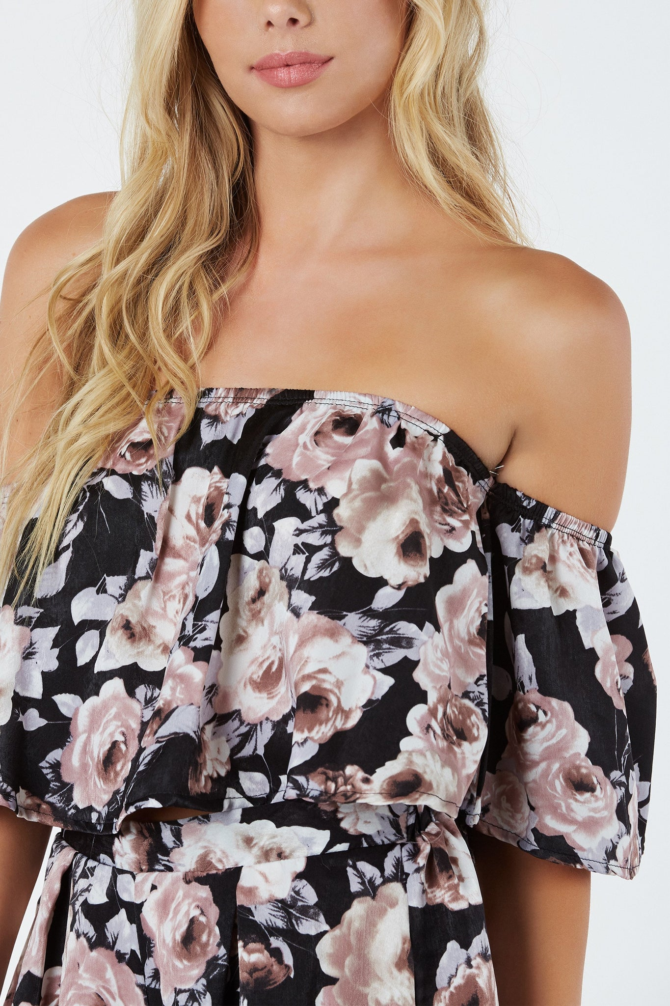 Chic off shoulder top with stain-like finish. Floral print throughout with flowy cropped hem finish.