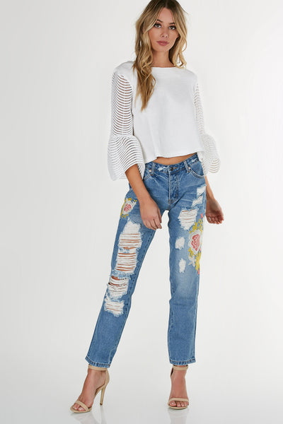 Mid rise mom style jeans with muted emboridered patches. Heavy distressing with vintage feel wash.